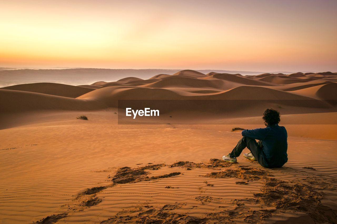 Man on sand dune in desert against sky during sunset