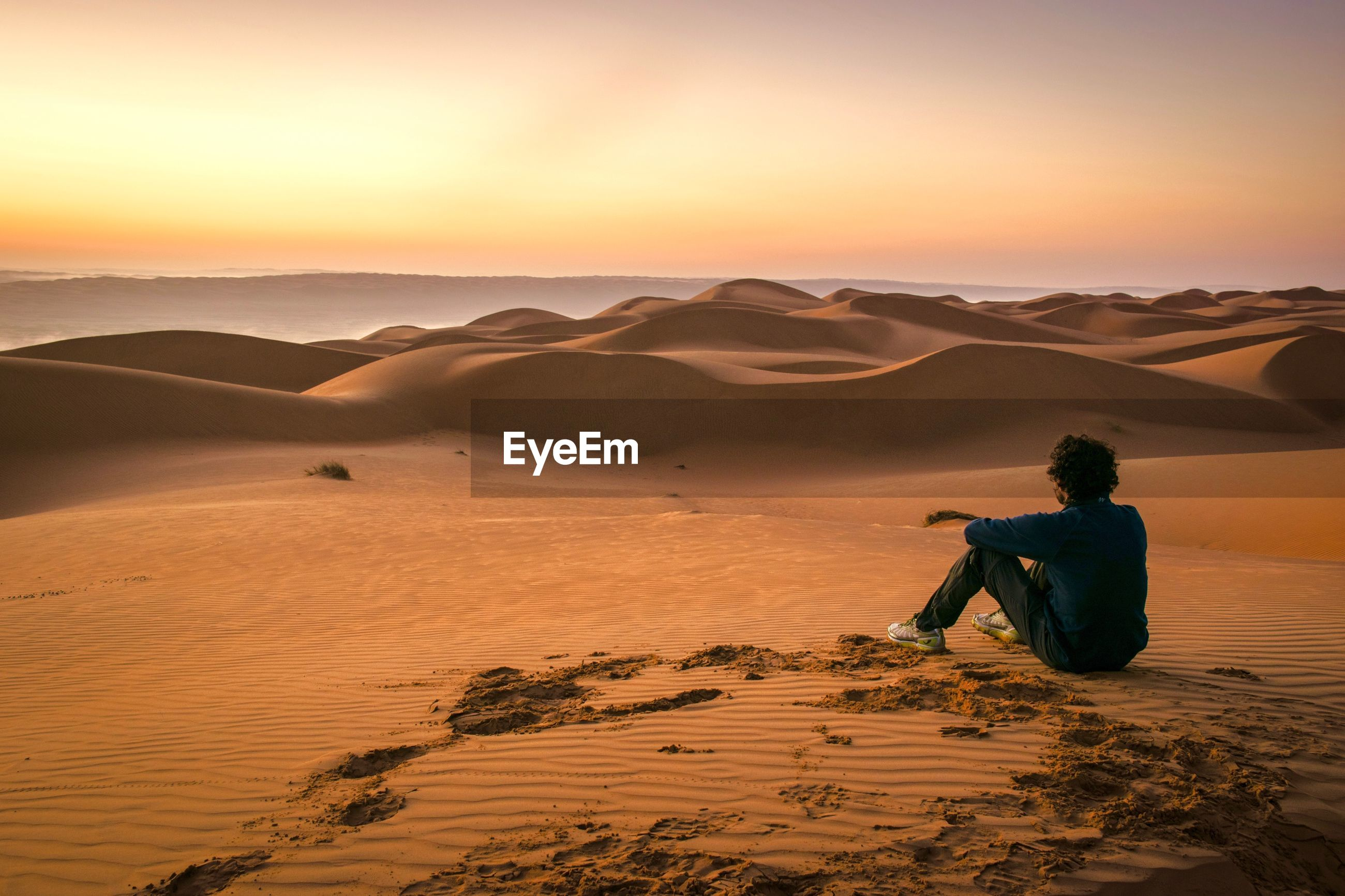 Man on sand dune in desert against sky during sunset