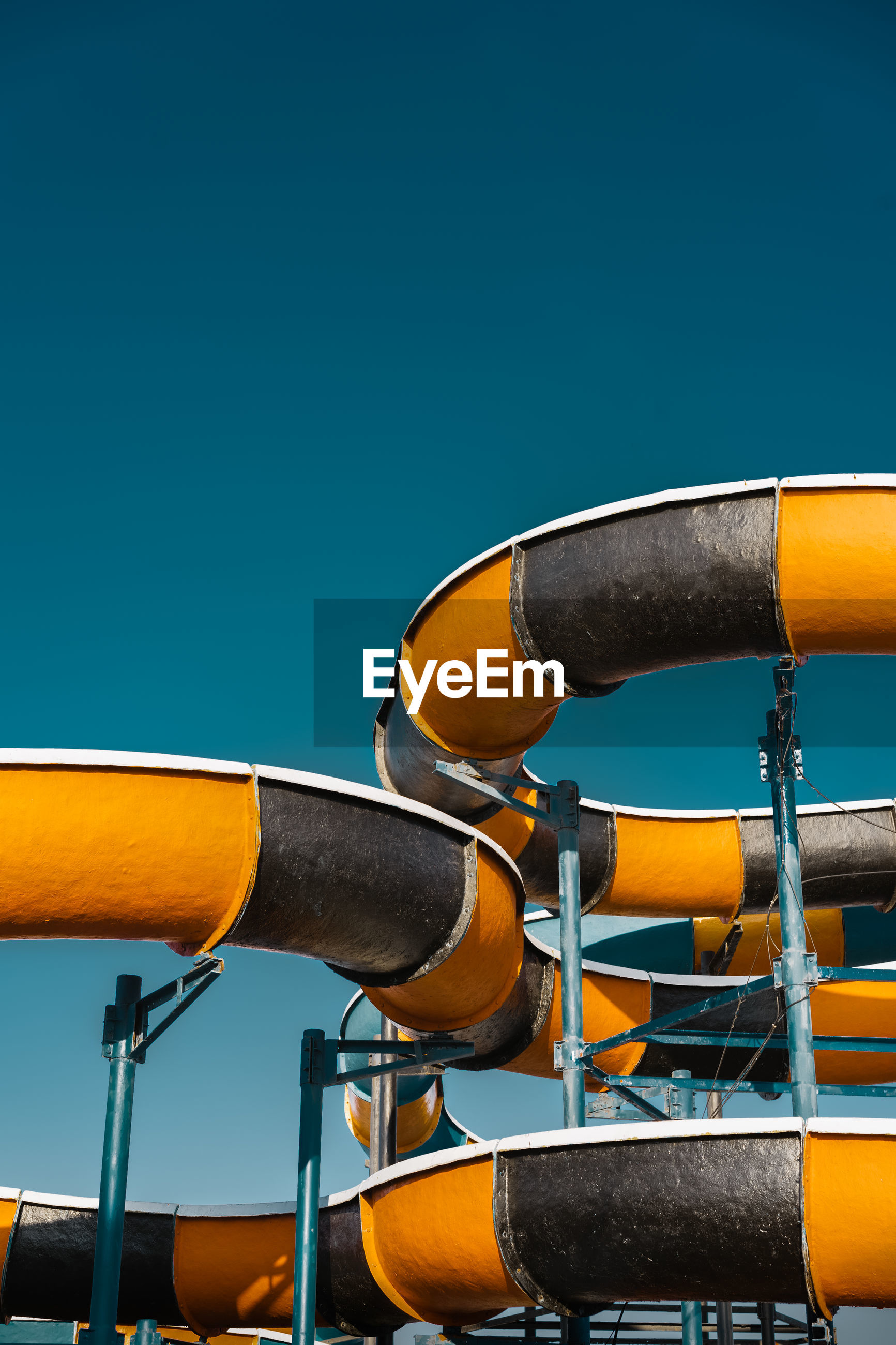 Low angle view of water slide against clear sky at amusement park