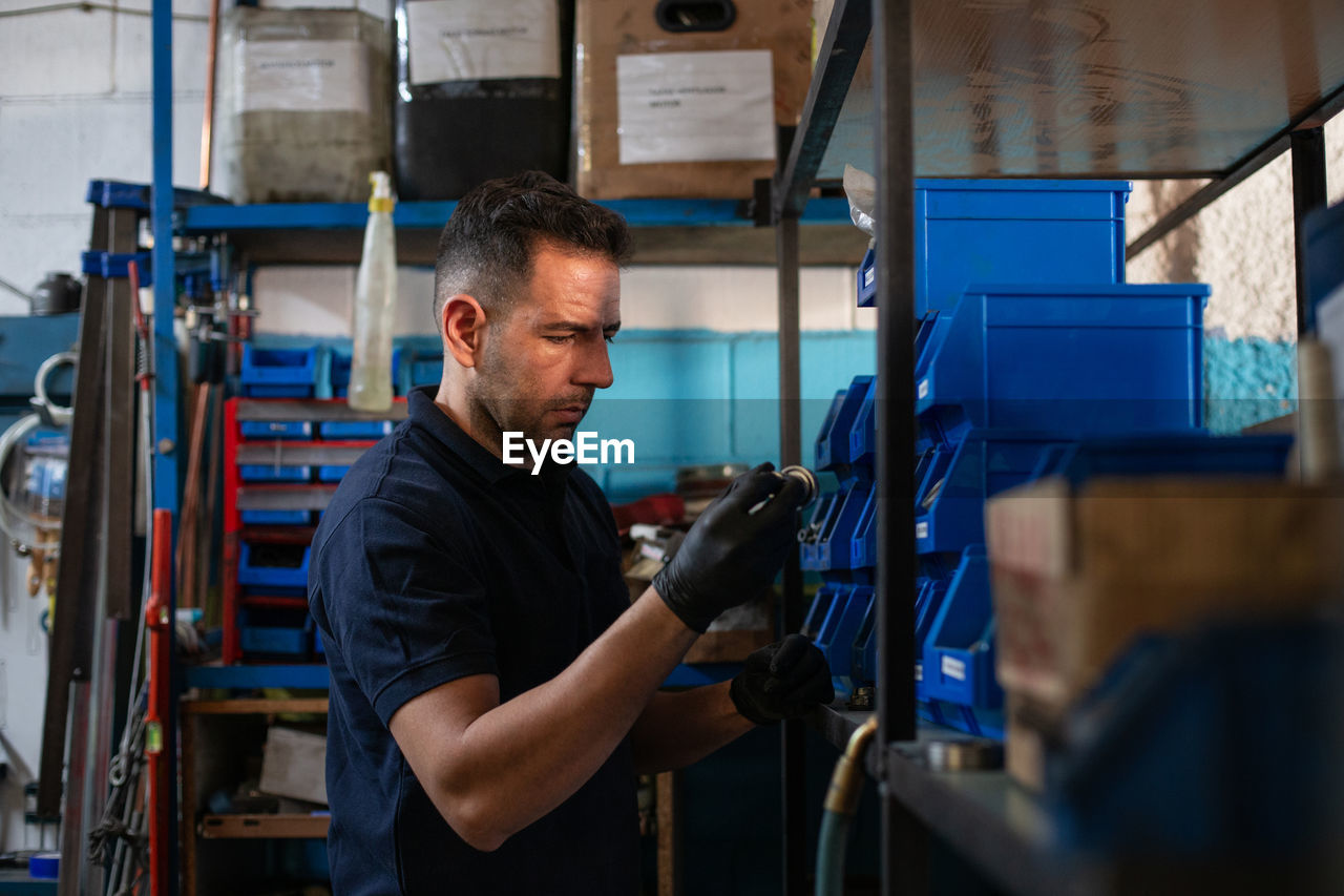 MAN WORKING IN FACTORY AT INDUSTRY