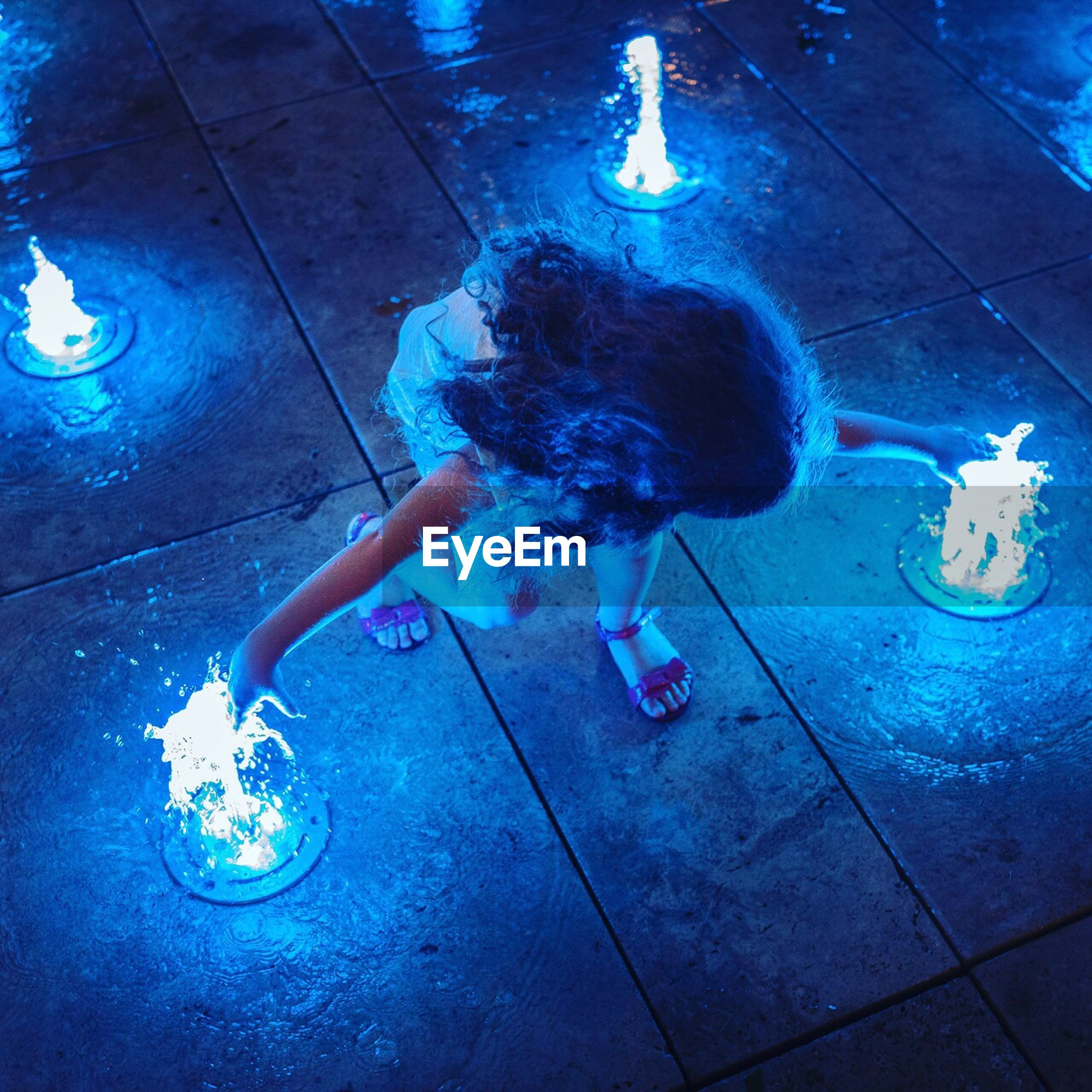 one person, real people, full length, illuminated, childhood, high angle view, lifestyles, night, indoors, crouching, playing, light bulb, water, young adult, people, adult