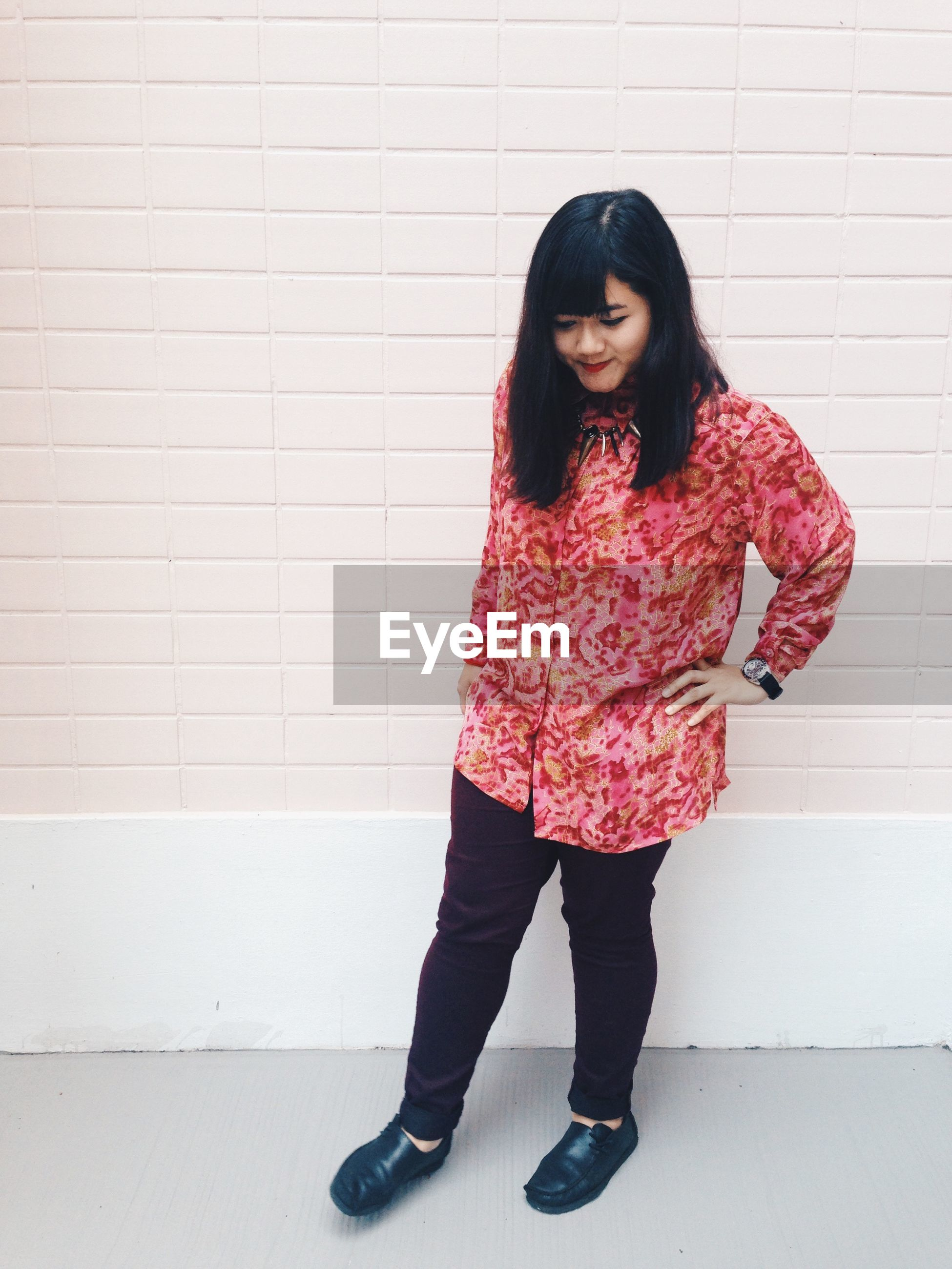 lifestyles, indoors, leisure activity, casual clothing, standing, wall - building feature, full length, young women, front view, holding, person, childhood, young adult, three quarter length, red, girls, fashion