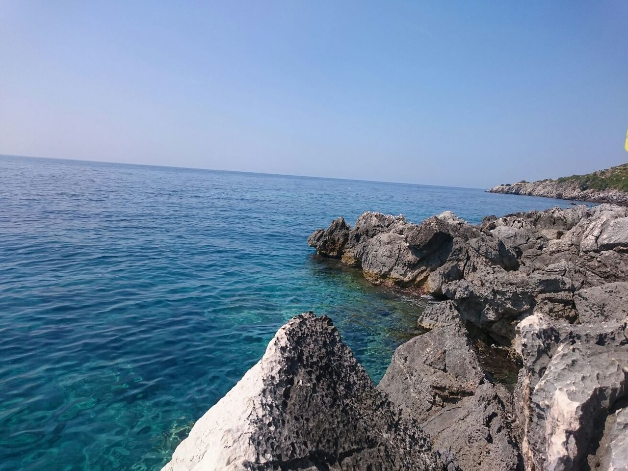 sea, horizon over water, nature, water, scenics, tranquil scene, beauty in nature, blue, tranquility, outdoors, rock - object, clear sky, day, no people, sky, beach