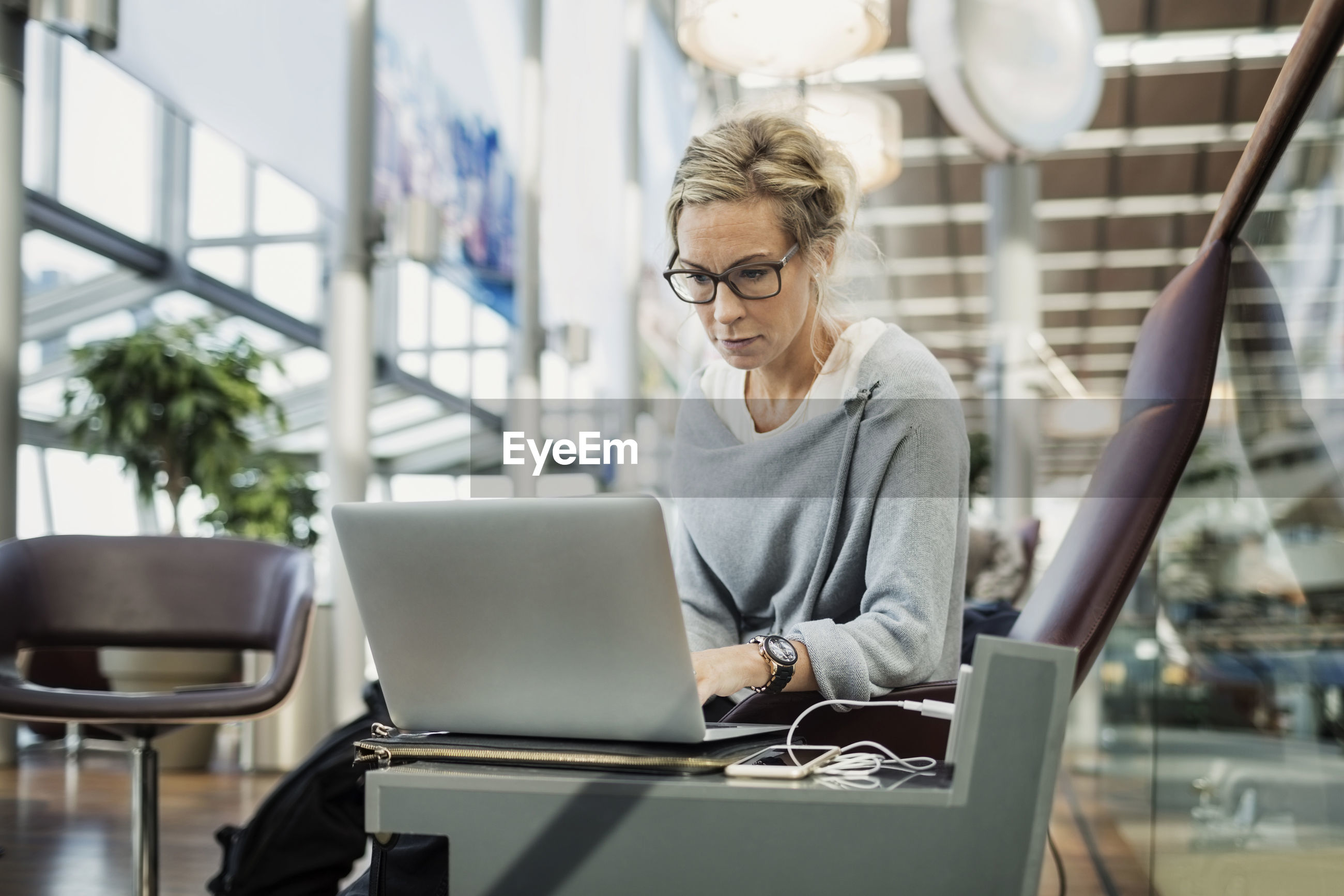 MIDSECTION OF WOMAN WORKING WITH LAPTOP
