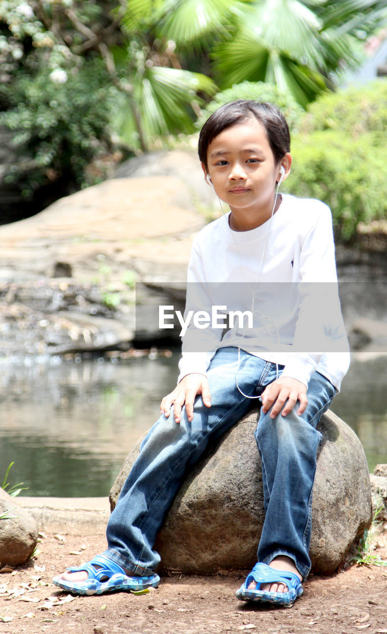 Portrait Of Boy Sitting On Rock By Lake
