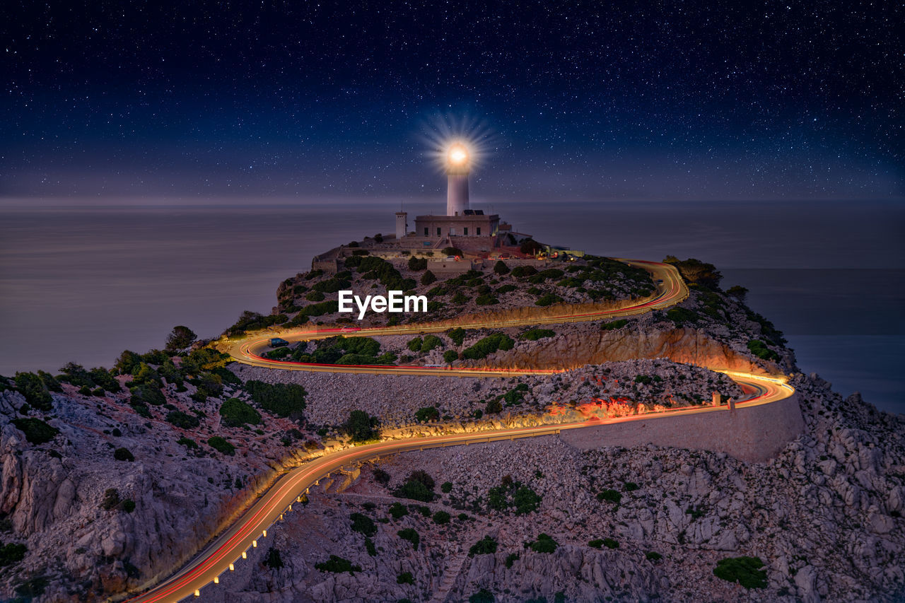 Scenic view of sea against sky at night mountain and lighthouse