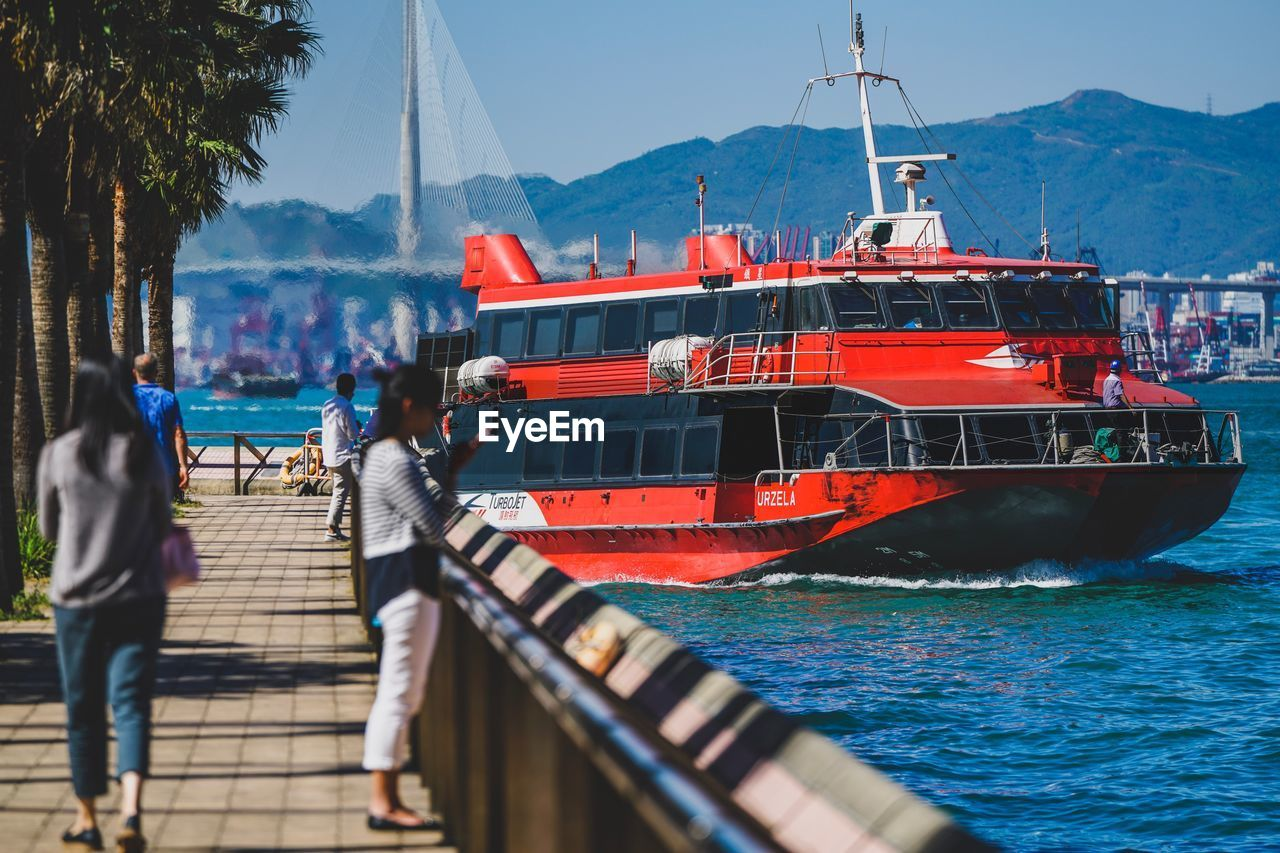 water, nautical vessel, transportation, mode of transportation, mountain, sea, incidental people, nature, day, sky, architecture, outdoors, red, real people, travel, built structure, ship, mountain range, sunlight, passenger craft, cruise ship