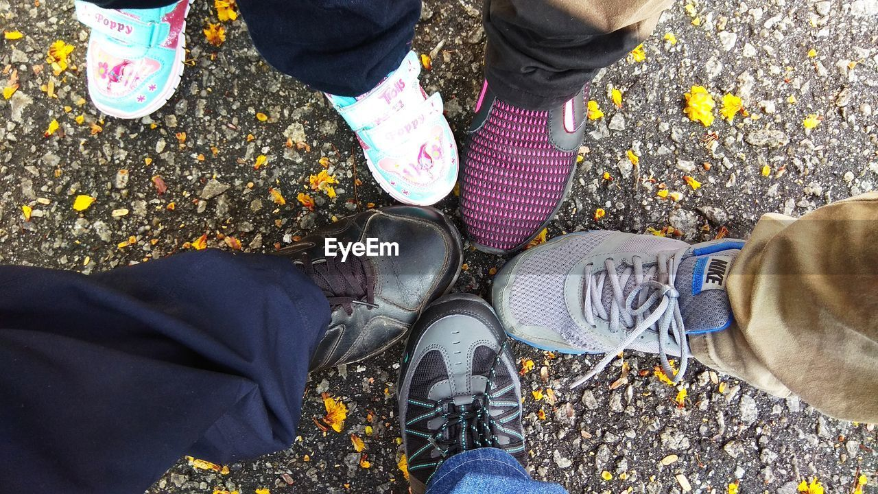 low section, real people, human leg, shoe, human body part, body part, standing, men, high angle view, lifestyles, personal perspective, day, people, group of people, street, leisure activity, nature, outdoors, city, human foot, pebble, human limb