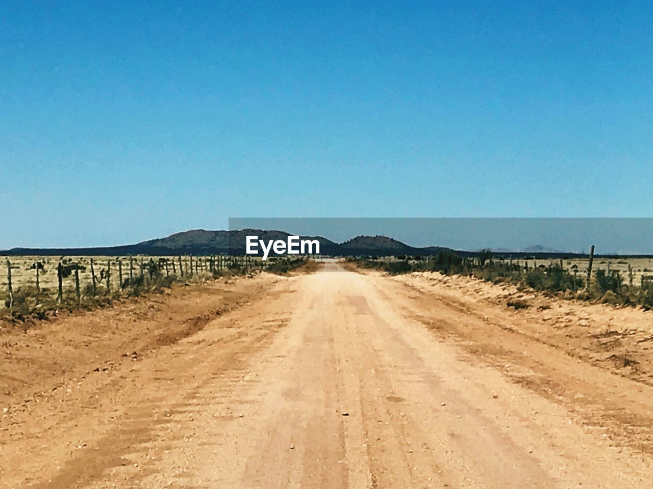 clear sky, landscape, the way forward, road, blue, copy space, no people, day, outdoors, transportation, sunlight, mountain, scenics, arid climate, nature, desert, sky