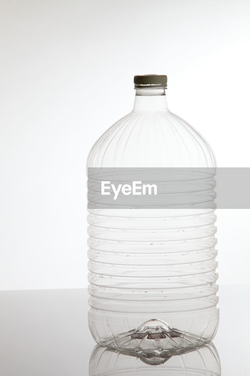 Close-Up Of Plastic Bottle On Table Against White Background