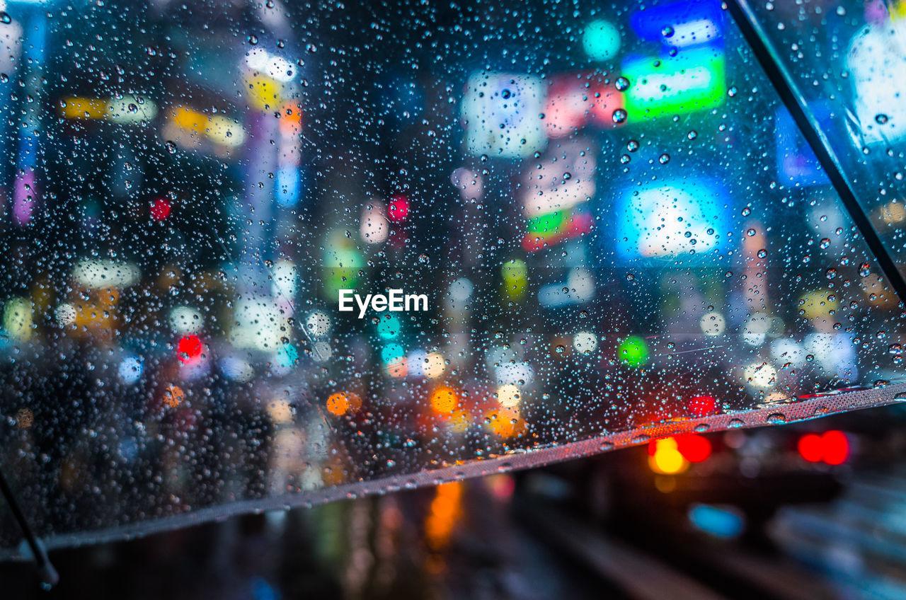 Road seen through wet umbrella during rainy season