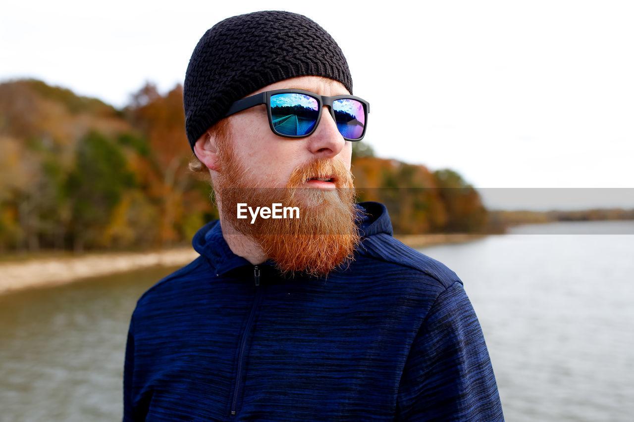 Bearded man standing against lake