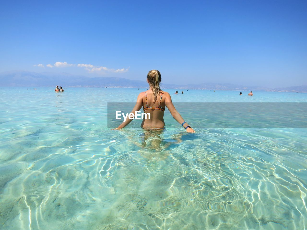 Rear View Of Woman In Sea Against Blue Sky