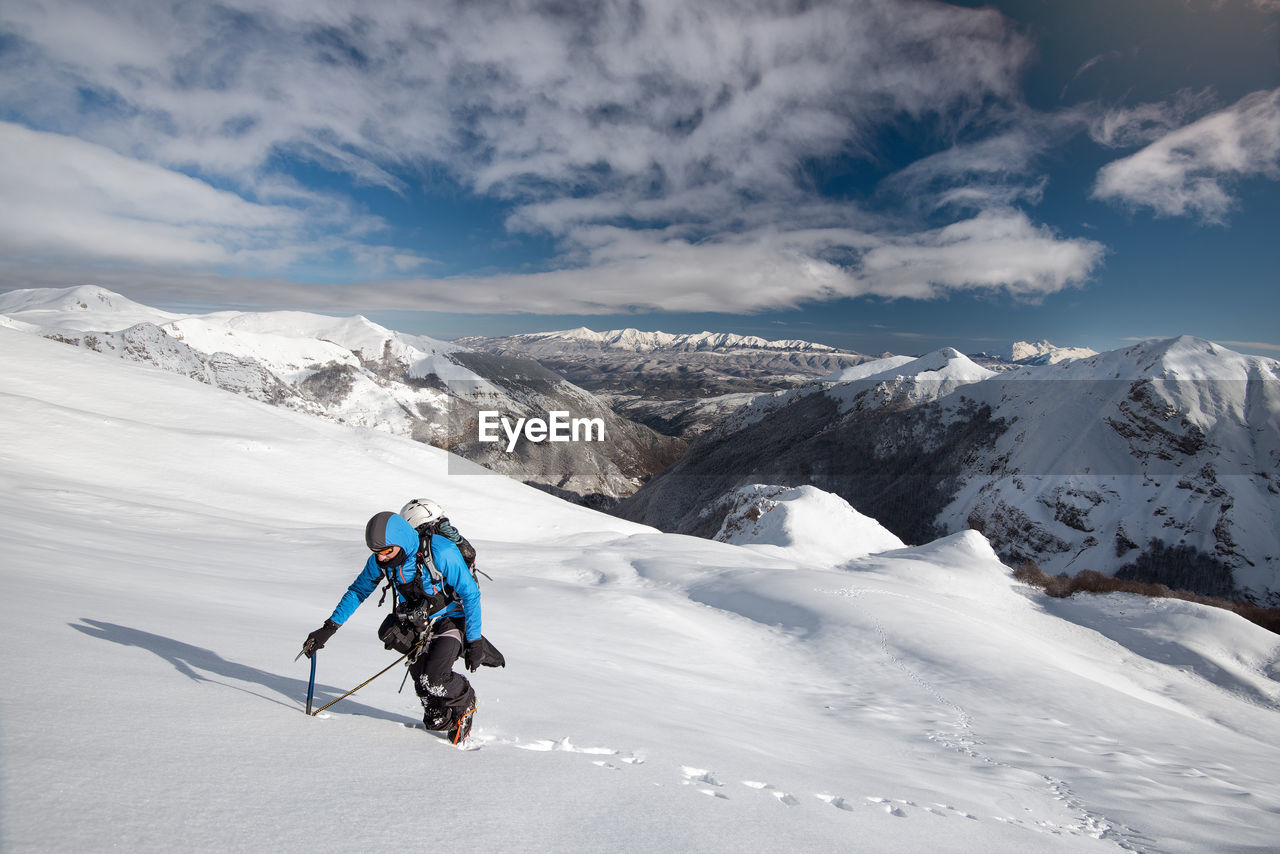 Man hiking snowcapped mountain against sky