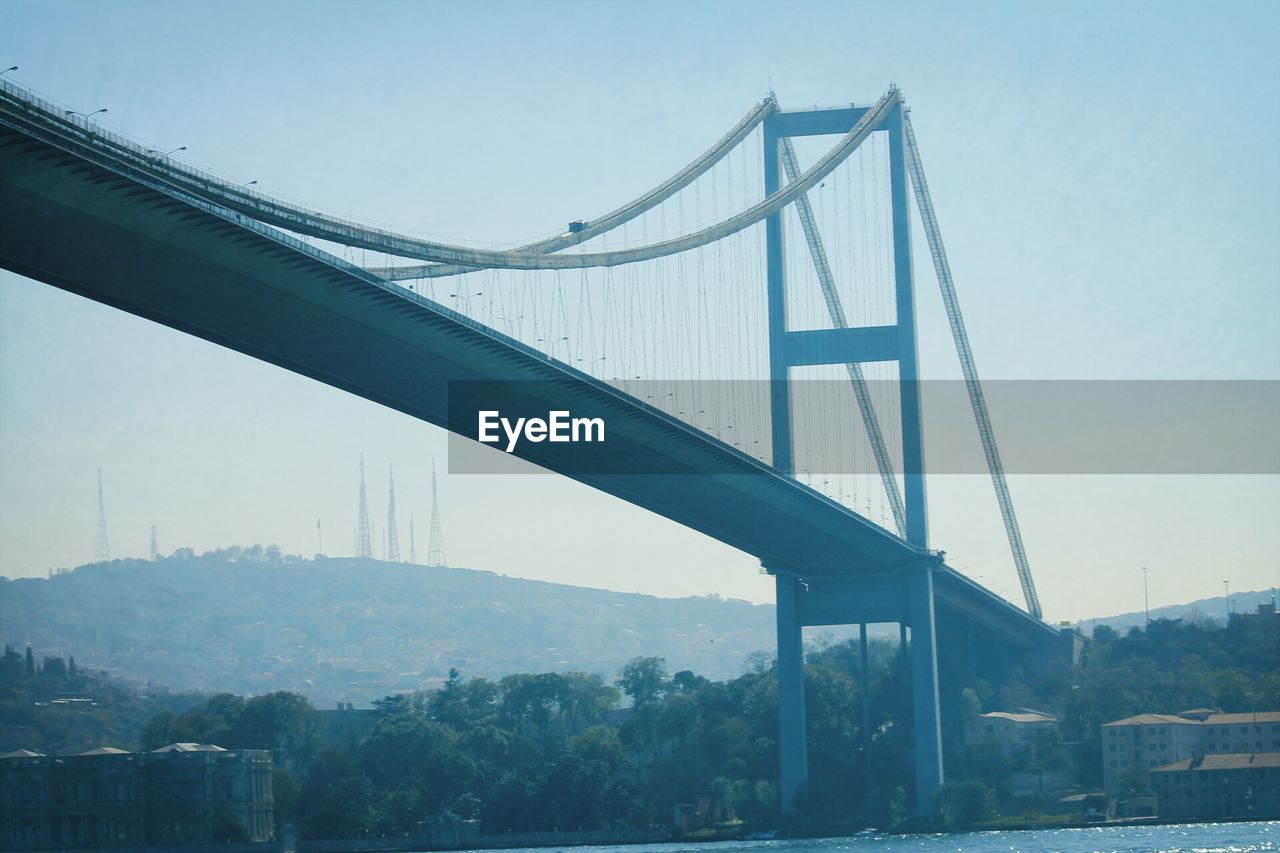 bridge - man made structure, connection, engineering, transportation, architecture, built structure, suspension bridge, tree, day, river, bridge, outdoors, no people, city, travel, travel destinations, low angle view, sky, road, fog, nature