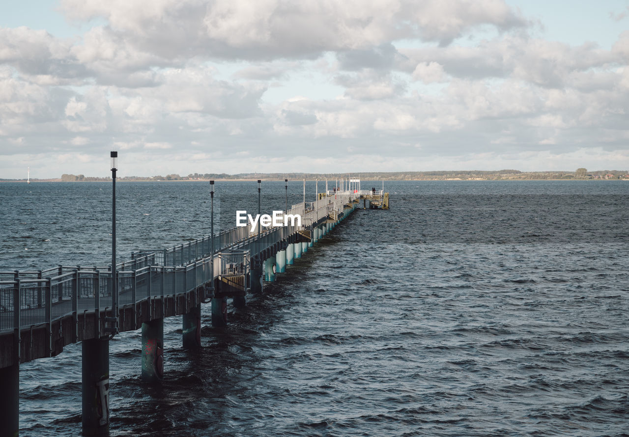 water, sky, sea, cloud - sky, scenics - nature, architecture, built structure, nature, tranquility, tranquil scene, day, railing, no people, horizon, beauty in nature, non-urban scene, pier, waterfront, wood - material, post, outdoors, horizon over water, wooden post, long