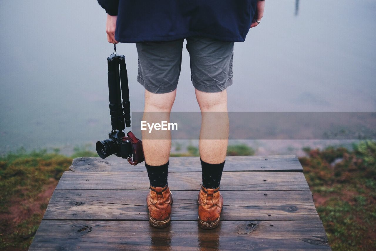 Low Section Of Man Holding Camera While Standing On Pier By Lake