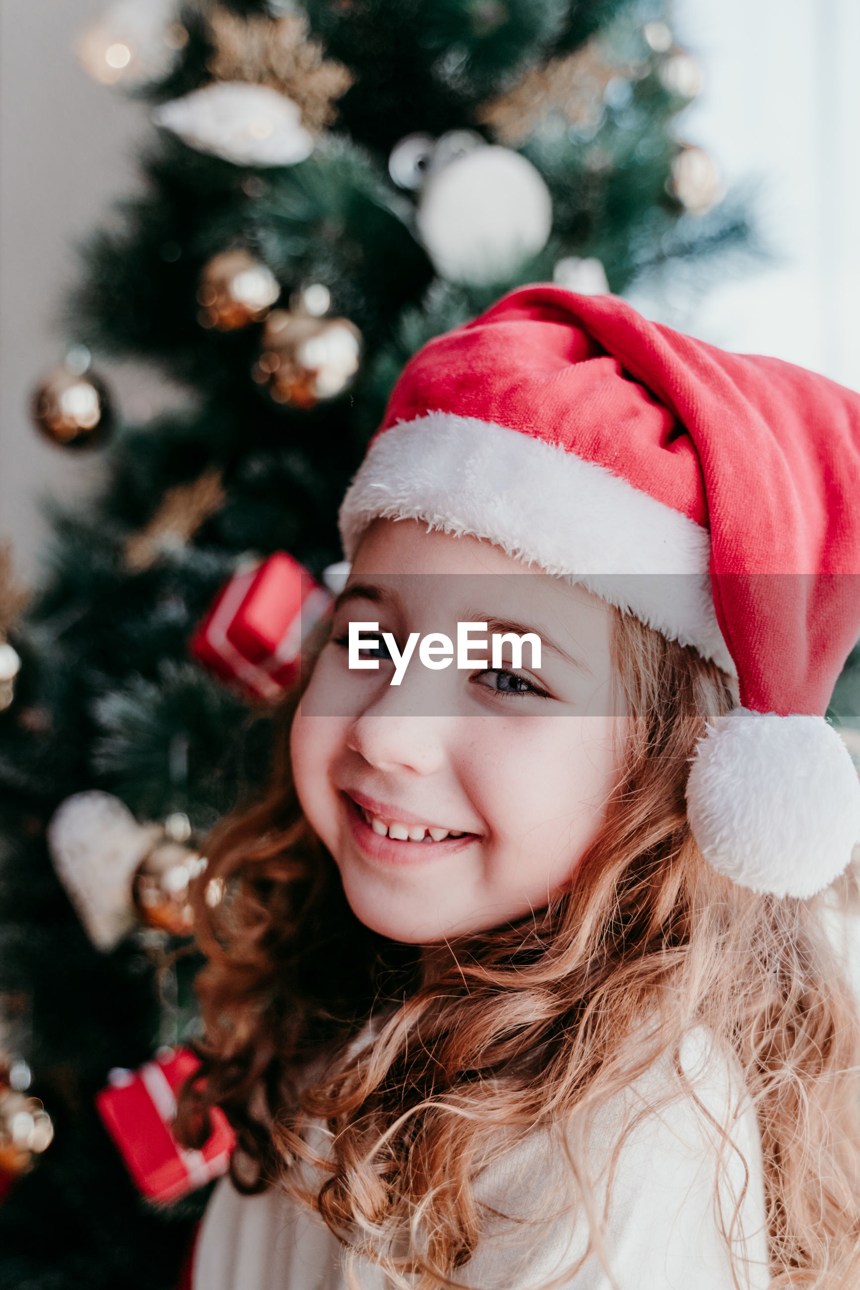 Portrait of smiling girl wearing santa hat by christmas tree