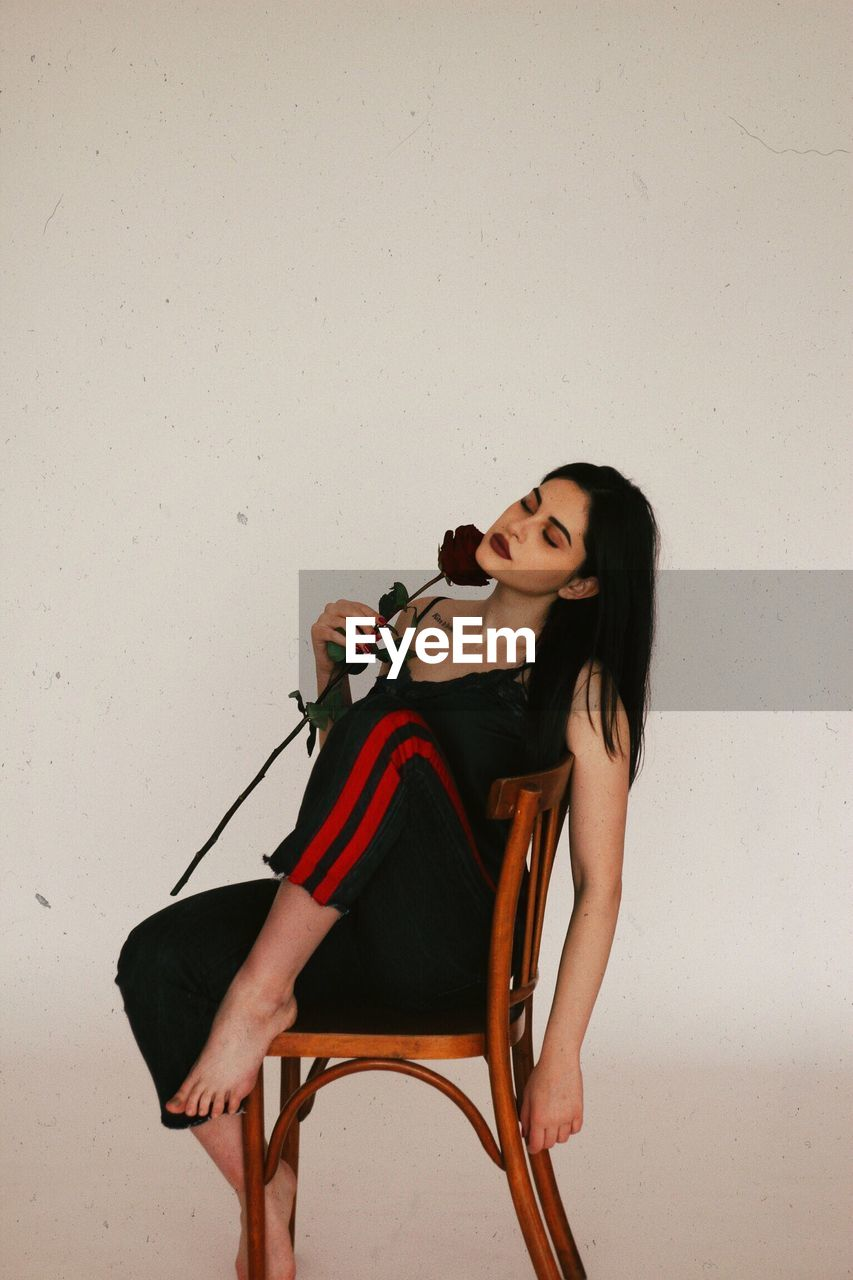 Sensuous woman holding rose while sitting on chair against white wall