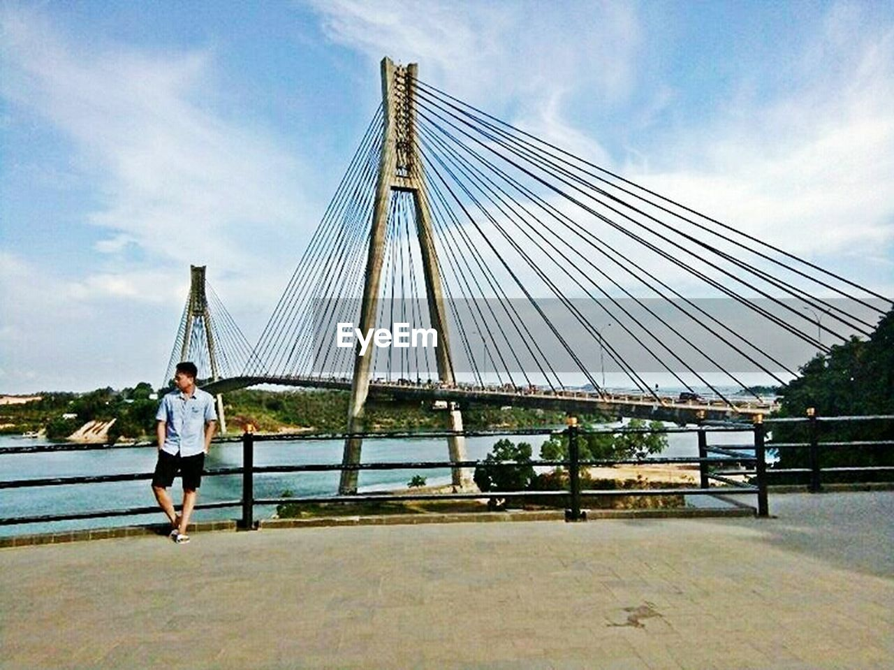 sky, cloud - sky, real people, one person, full length, bridge - man made structure, leisure activity, day, lifestyles, casual clothing, outdoors, built structure, architecture, men, suspension bridge, young adult, tree, nature, adult, adults only, people