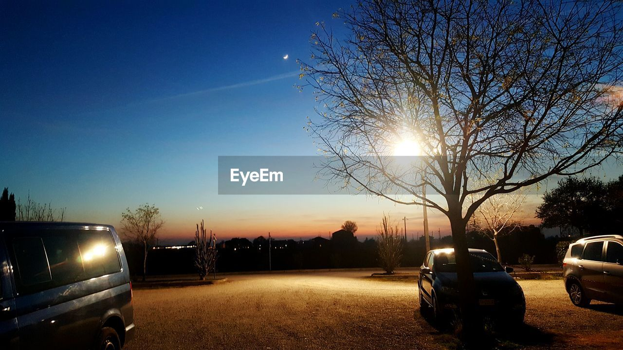bare tree, tree, sun, transportation, car, land vehicle, sky, outdoors, road, sunset, nature, no people, branch, illuminated, clear sky, beauty in nature, day