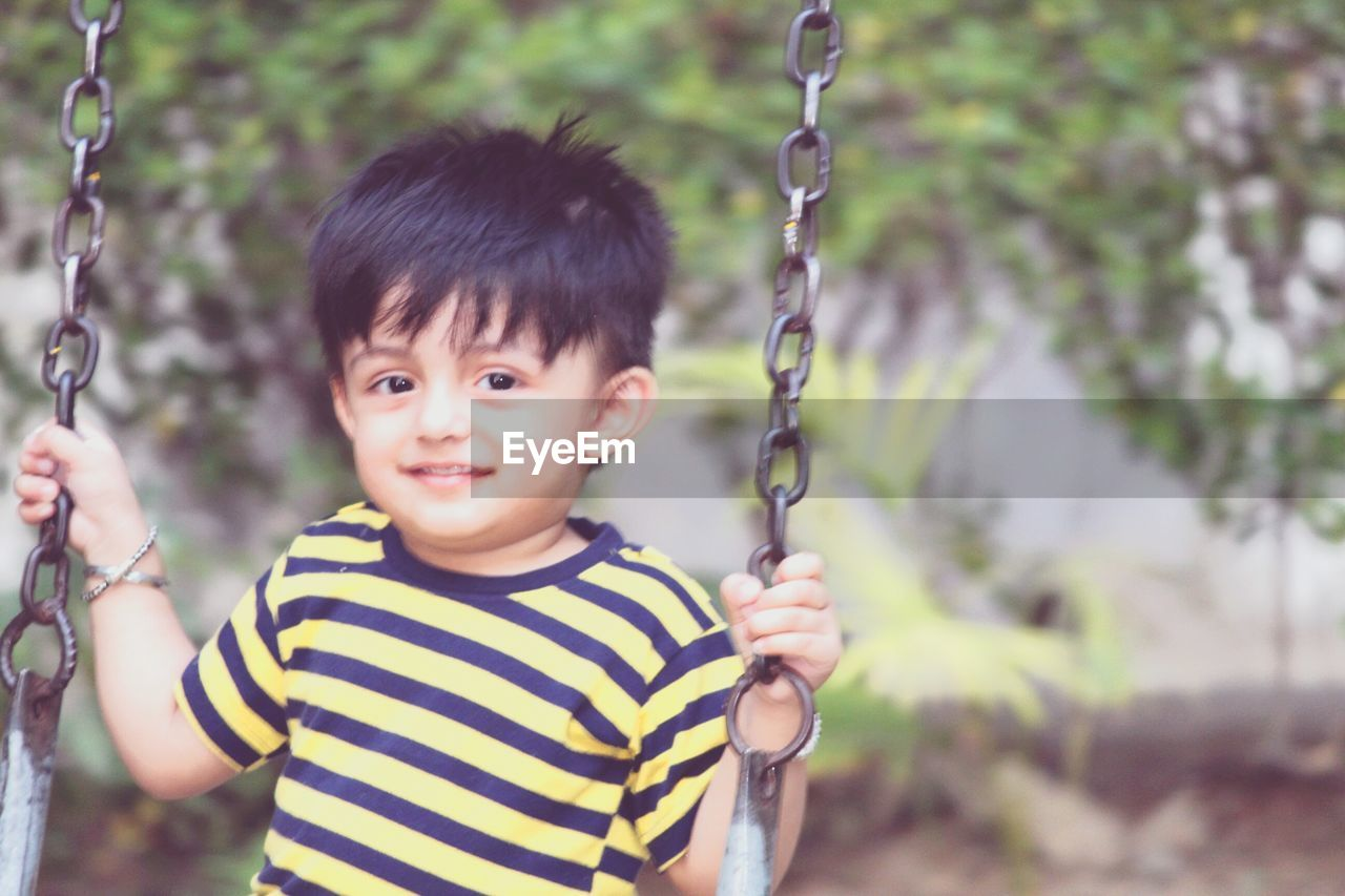childhood, swing, striped, one person, real people, playground, looking at camera, casual clothing, innocence, outdoors, focus on foreground, day, happiness, fun, portrait, smiling, hanging, boys, rope swing, close-up, people