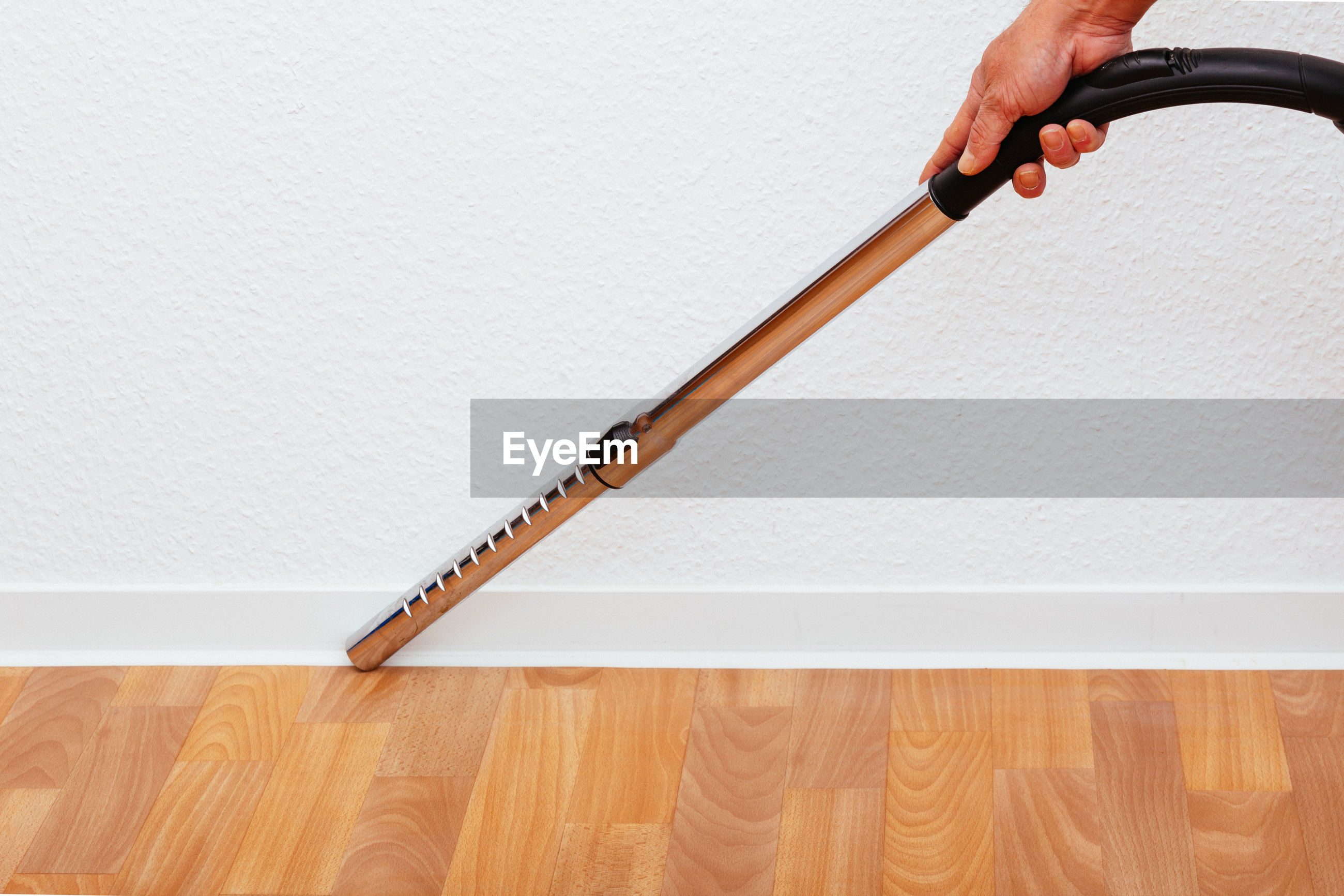 Cropped hand holding vacuum cleaner against white wall
