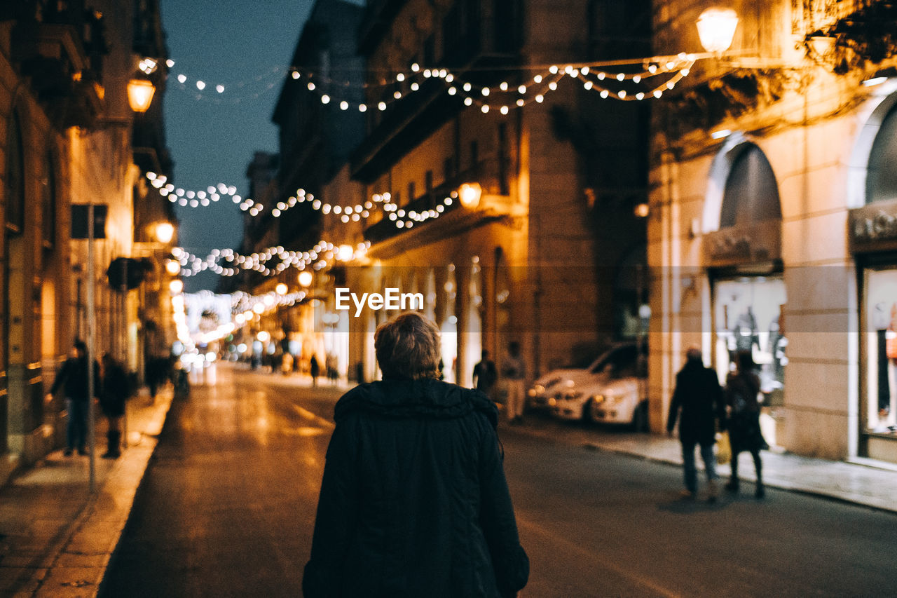 REAR VIEW OF WOMAN WALKING ON ILLUMINATED STREET IN CITY
