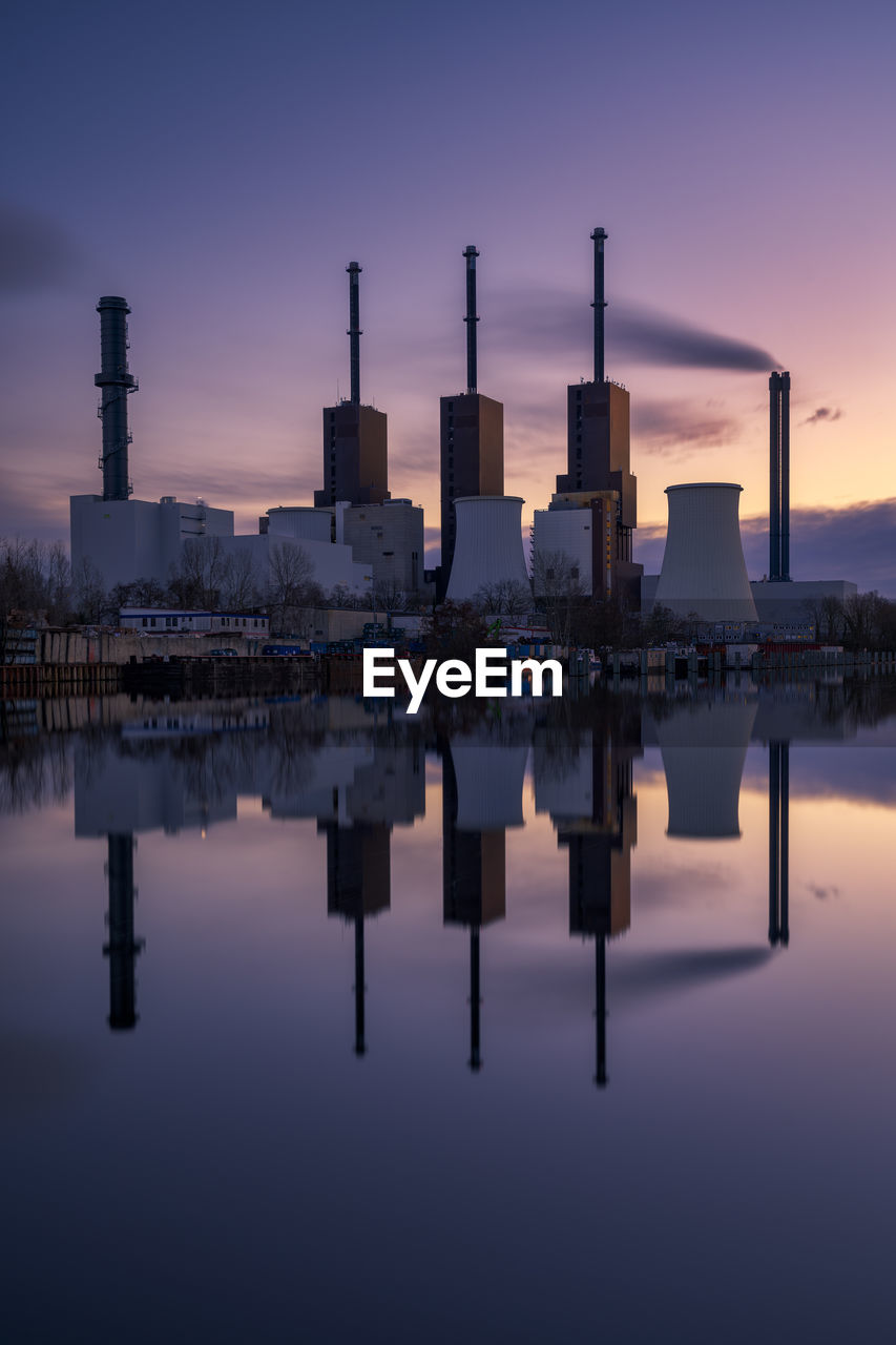 waterfront, sky, built structure, architecture, building exterior, water, reflection, sunset, nature, factory, no people, industry, lake, outdoors, smoke stack, city, standing water, building, pollution