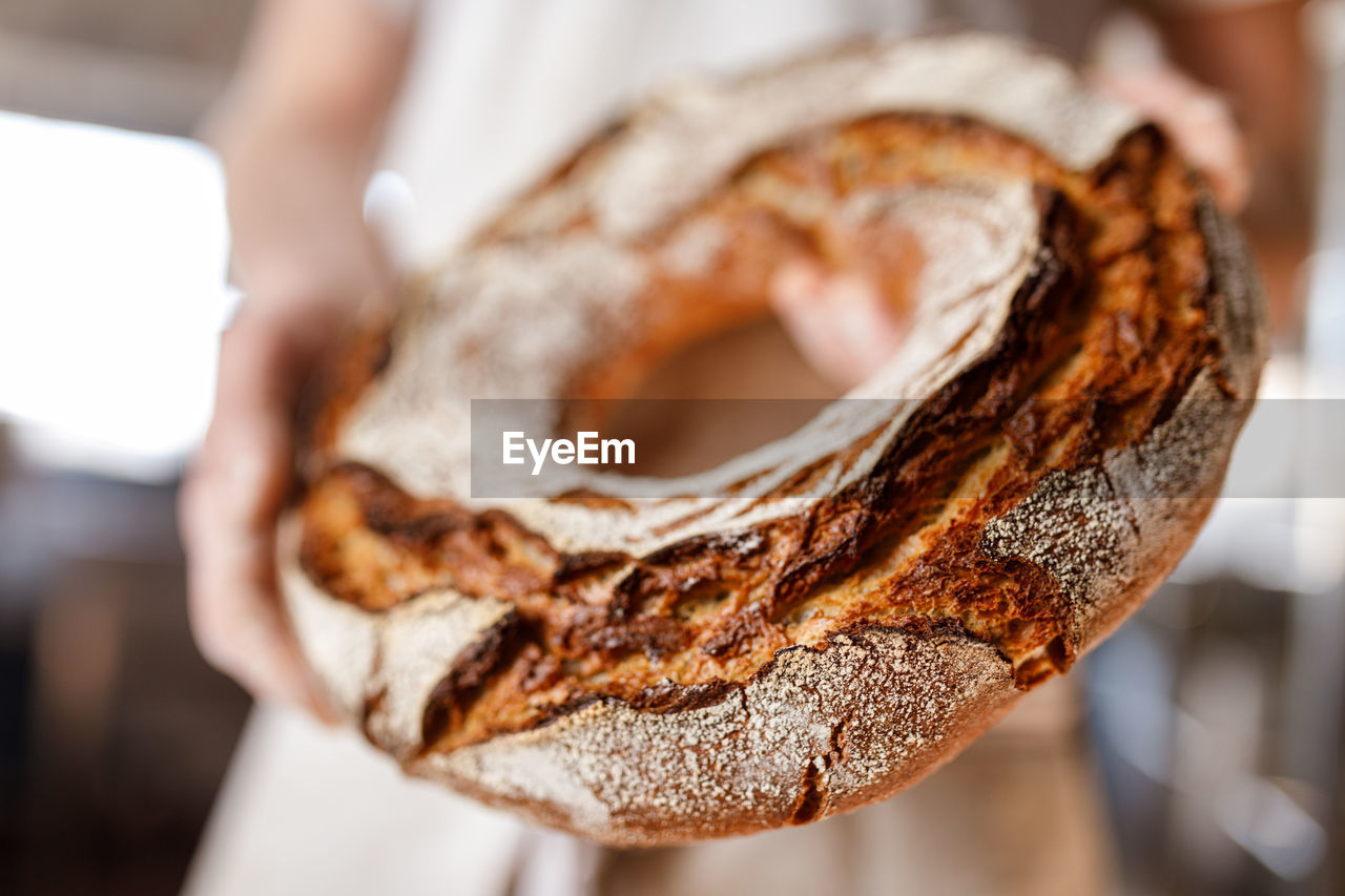 CLOSE-UP OF HAND HOLDING BREAD IN CONTAINER