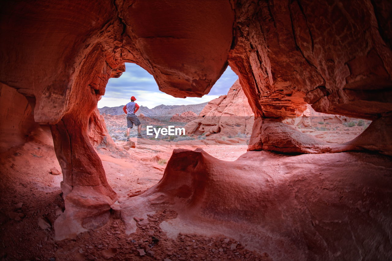 Rear view of man standing on rock seen from cave at valley of fire state park