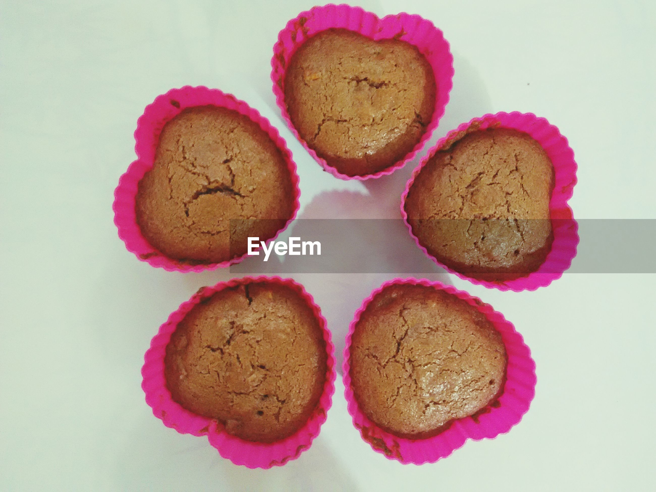 Directly above view of fresh heart shape cupcakes on white background