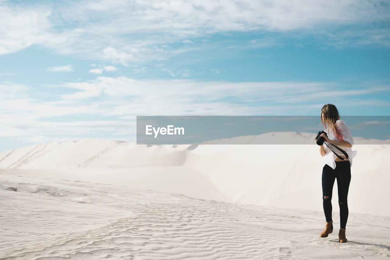 Woman standing on sand dune at beach