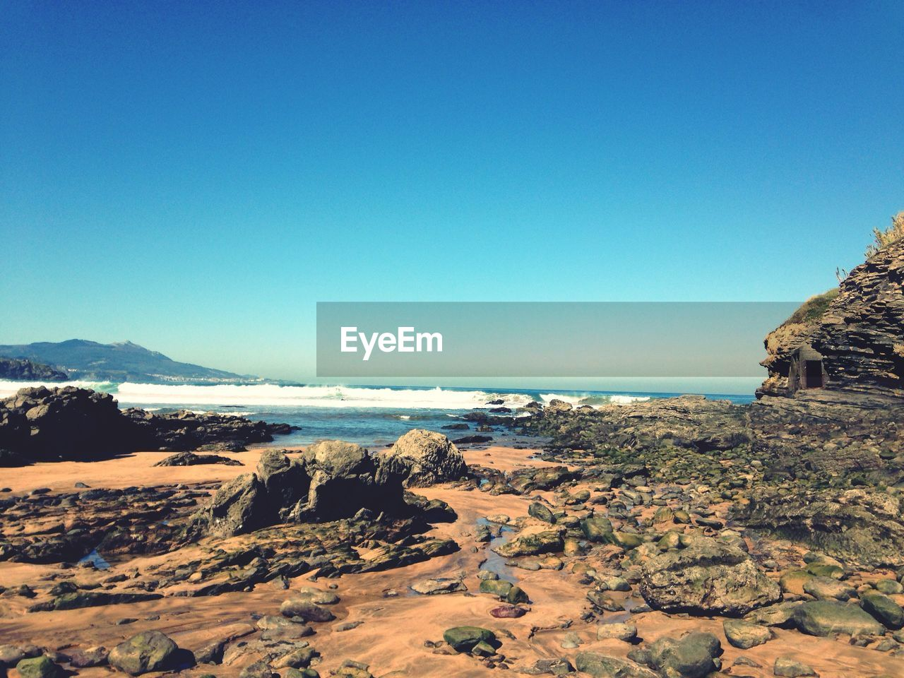 Scenic View Of Sea And Beach Against Clear Sky