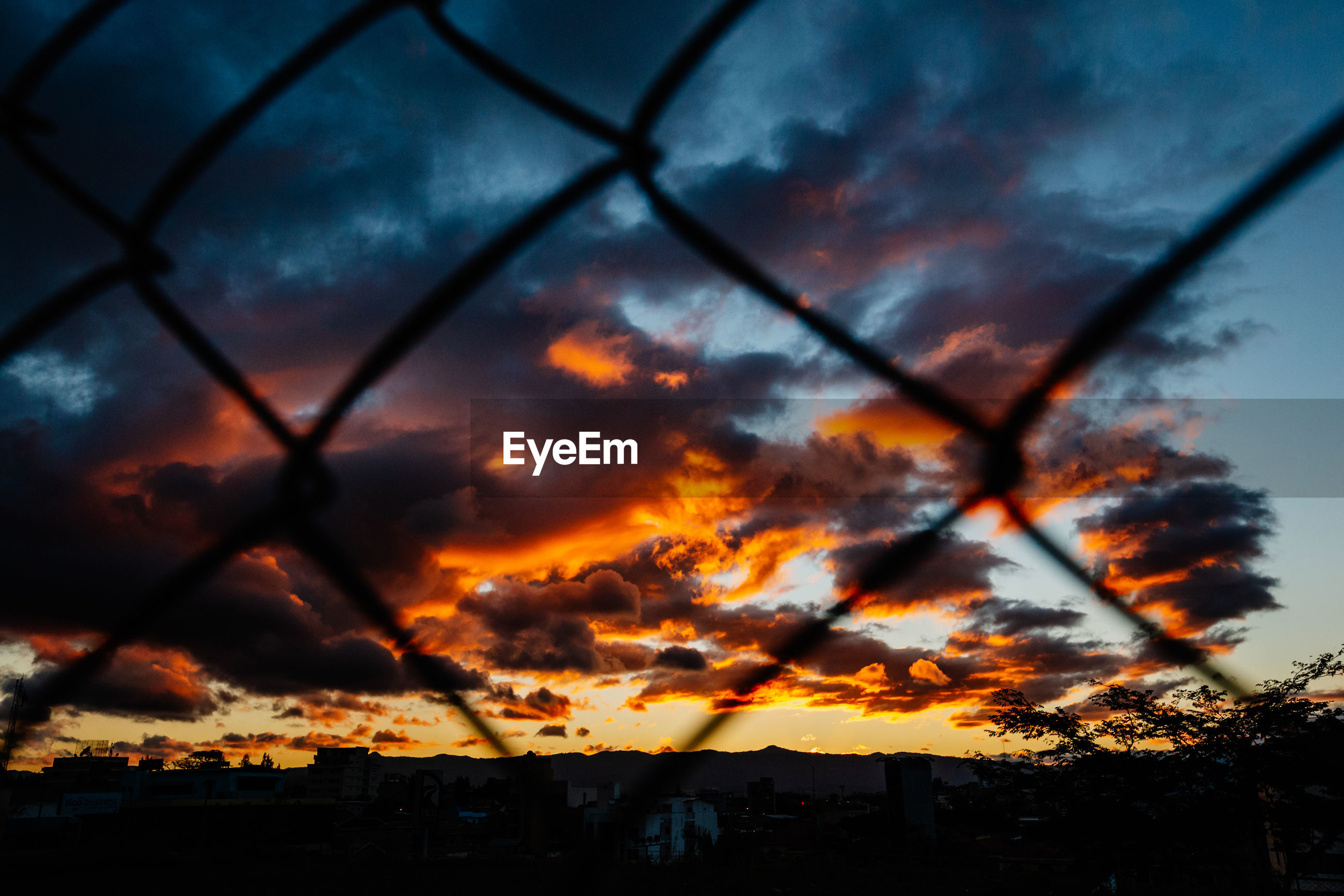 Cloudy sky seen through chainlink fence during sunset