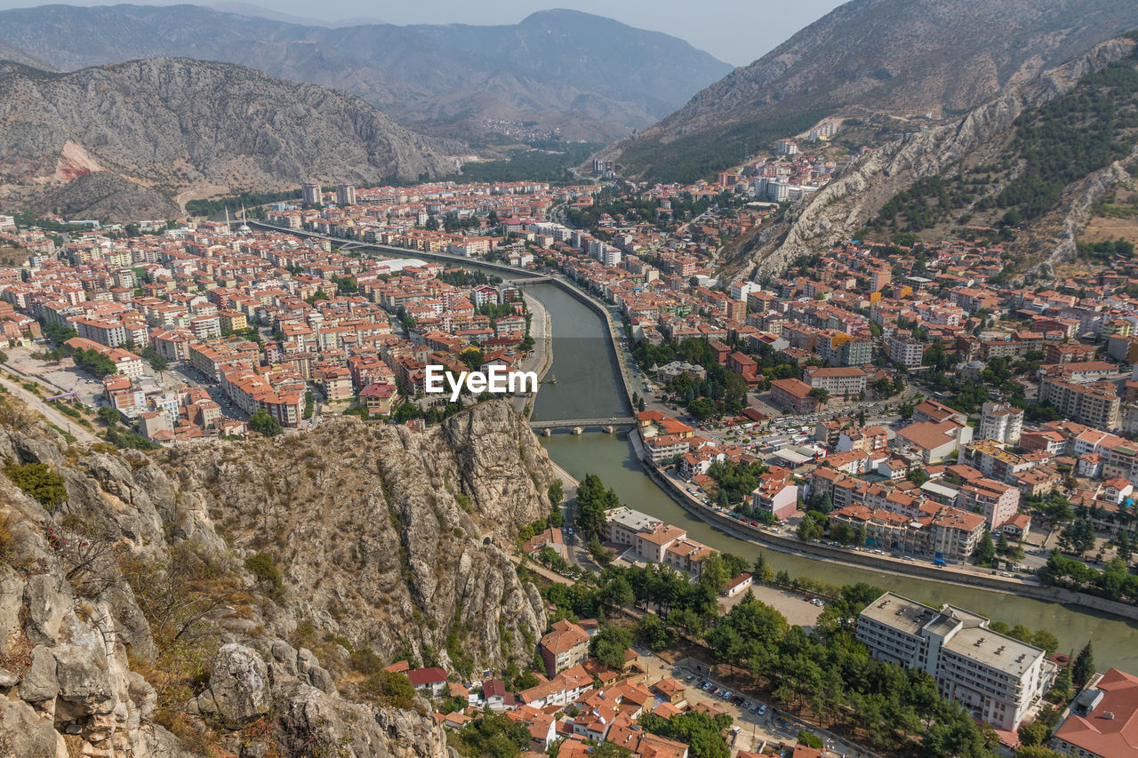 architecture, built structure, building exterior, mountain, city, residential district, high angle view, town, nature, building, day, water, cityscape, no people, outdoors, aerial view, connection, tree, scenics - nature, transportation, townscape