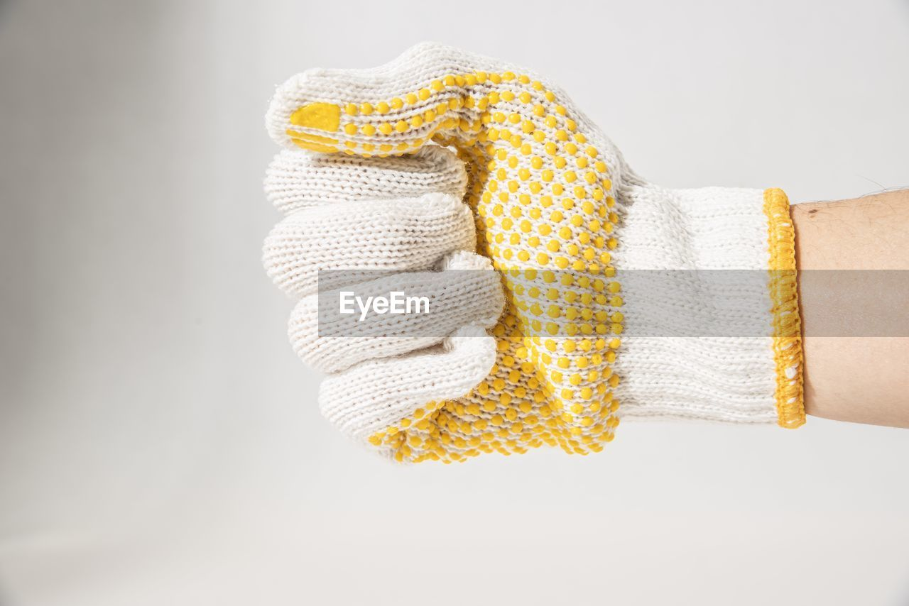 Cropped hand of person wearing knit glove against white background