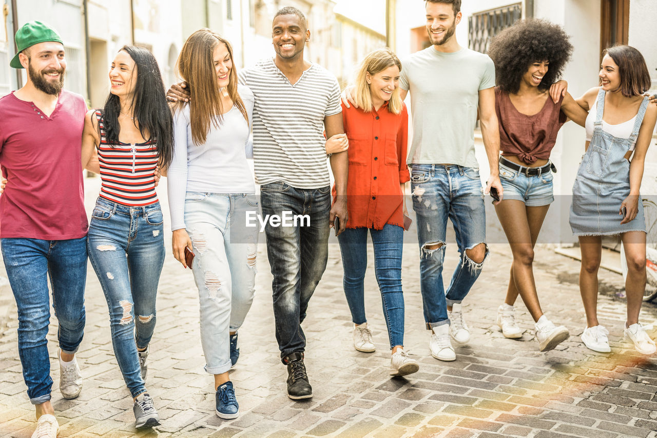 Full Length Of Young Friends Walking On Footpath In City