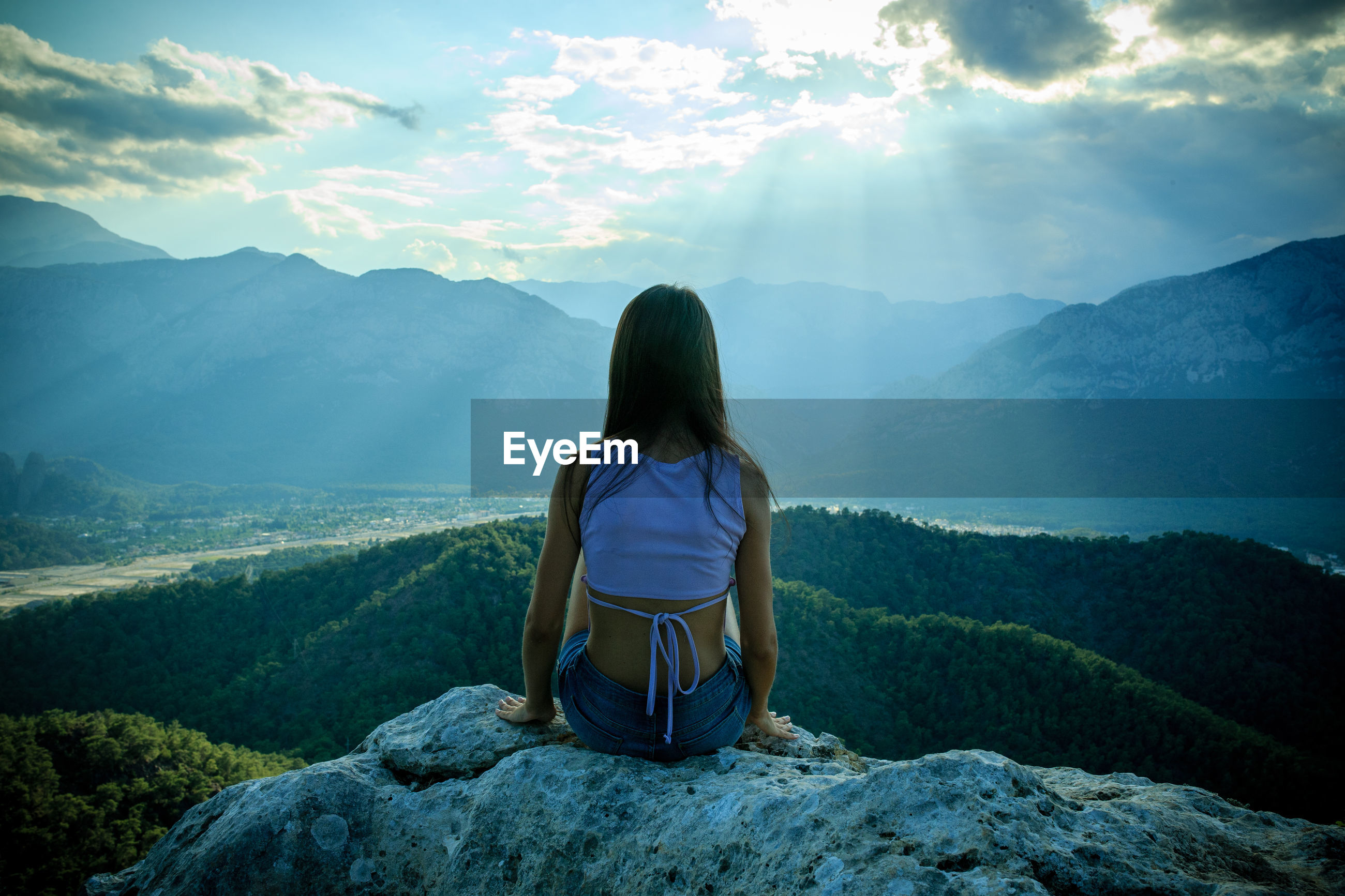 Rear view of woman sitting on rock against mountains