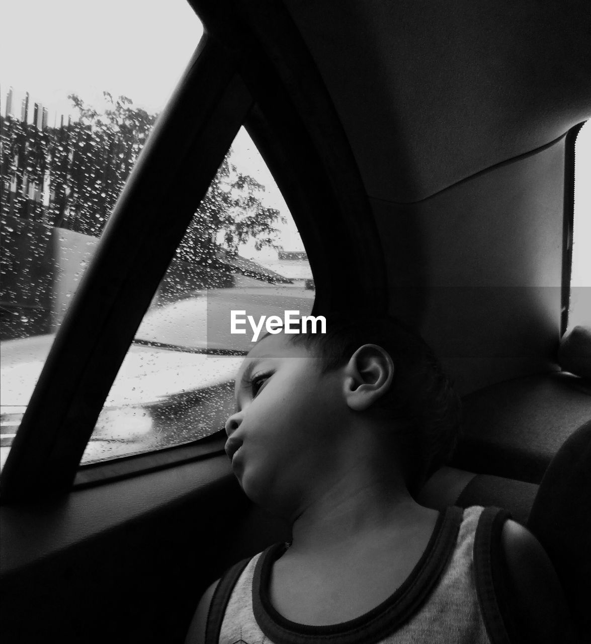 Close-Up Of Boy Looking Through Window In Car