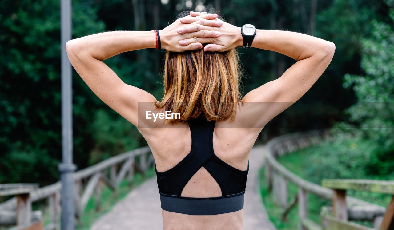Rear view of woman exercising in park
