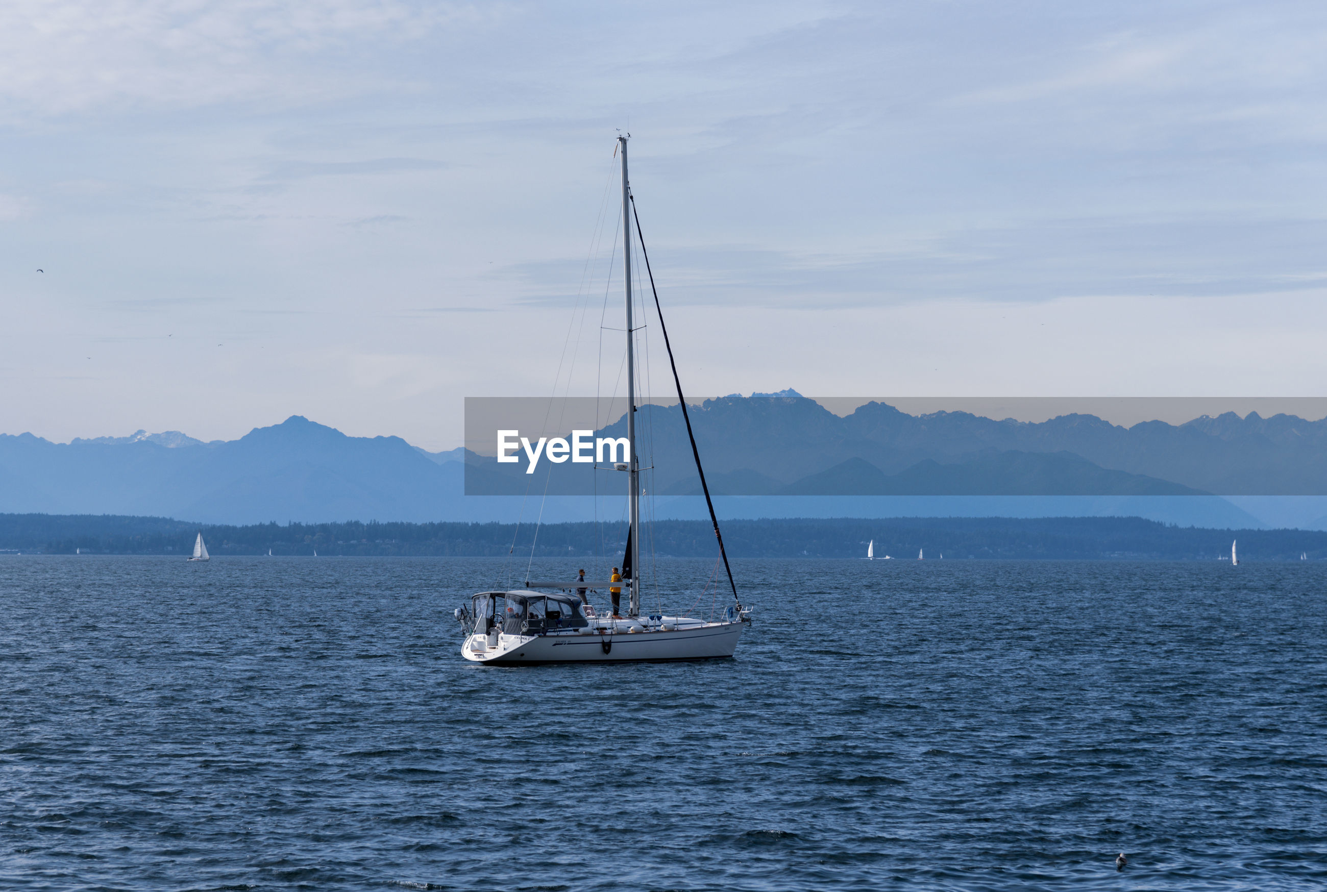 Sailboat off shore mid day sun with olympic mountains and people standing on deck.