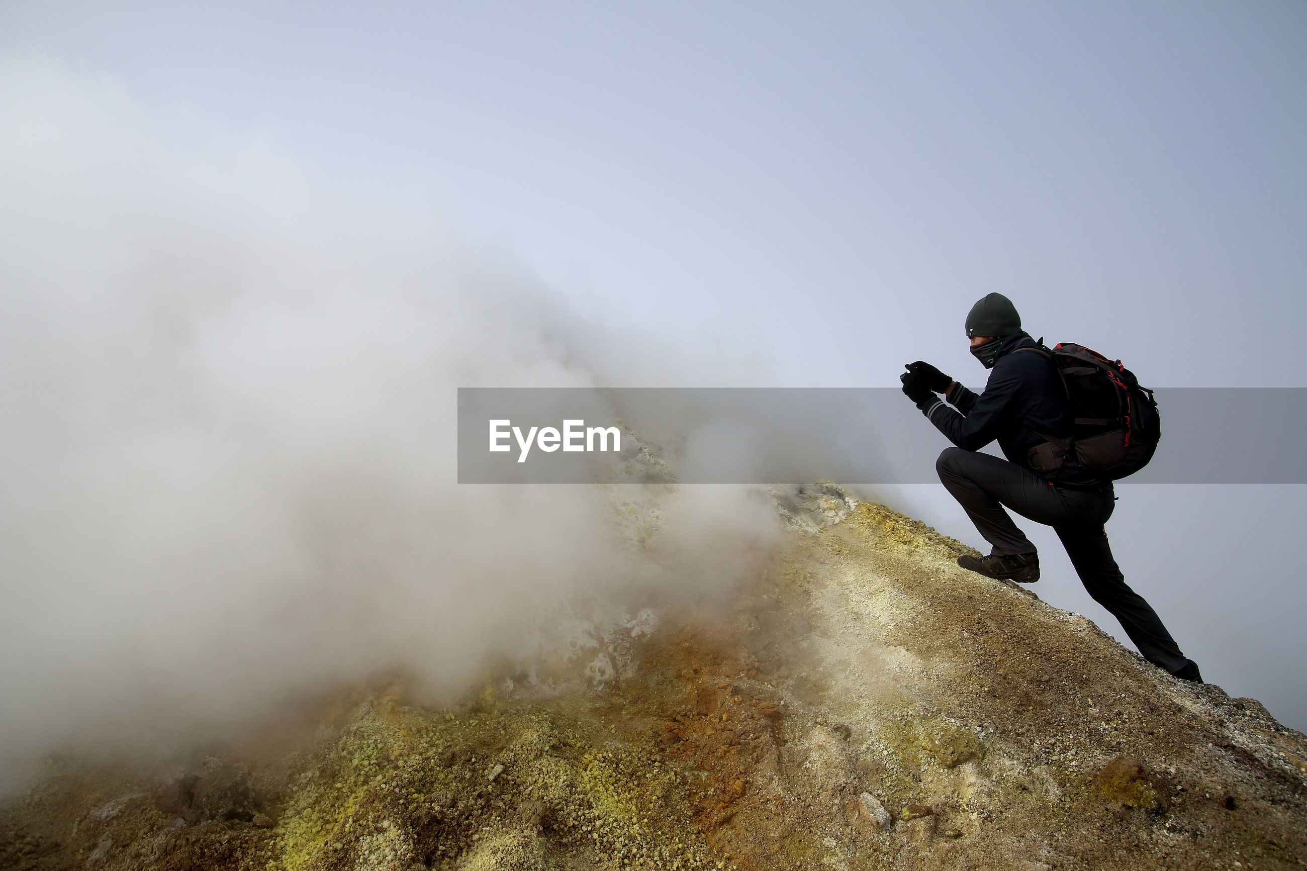 Man climbing mt etna against sky