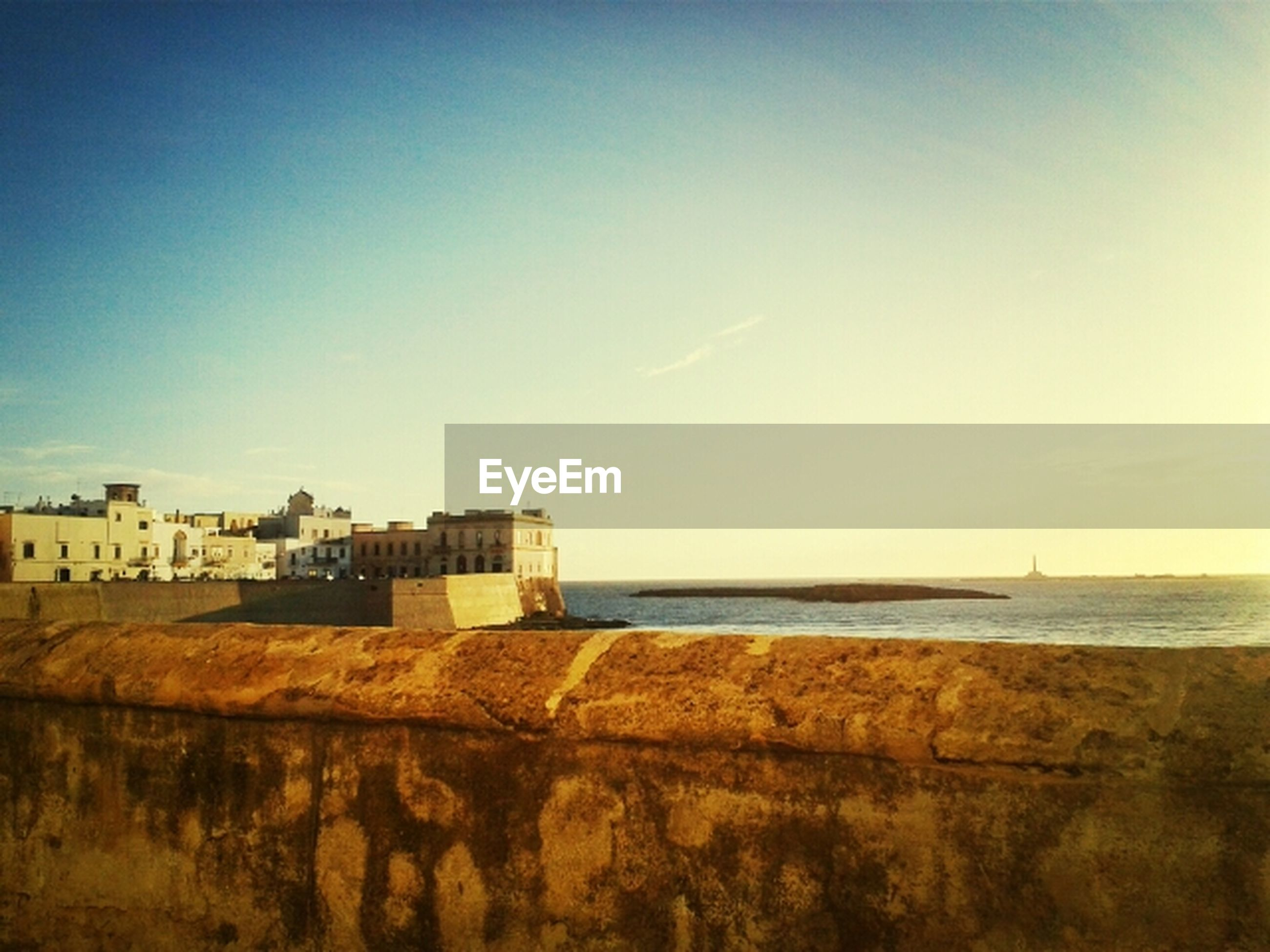 sea, horizon over water, water, built structure, building exterior, copy space, architecture, clear sky, beach, blue, tranquil scene, sky, scenics, tranquility, shore, beauty in nature, nature, day, outdoors, sunlight