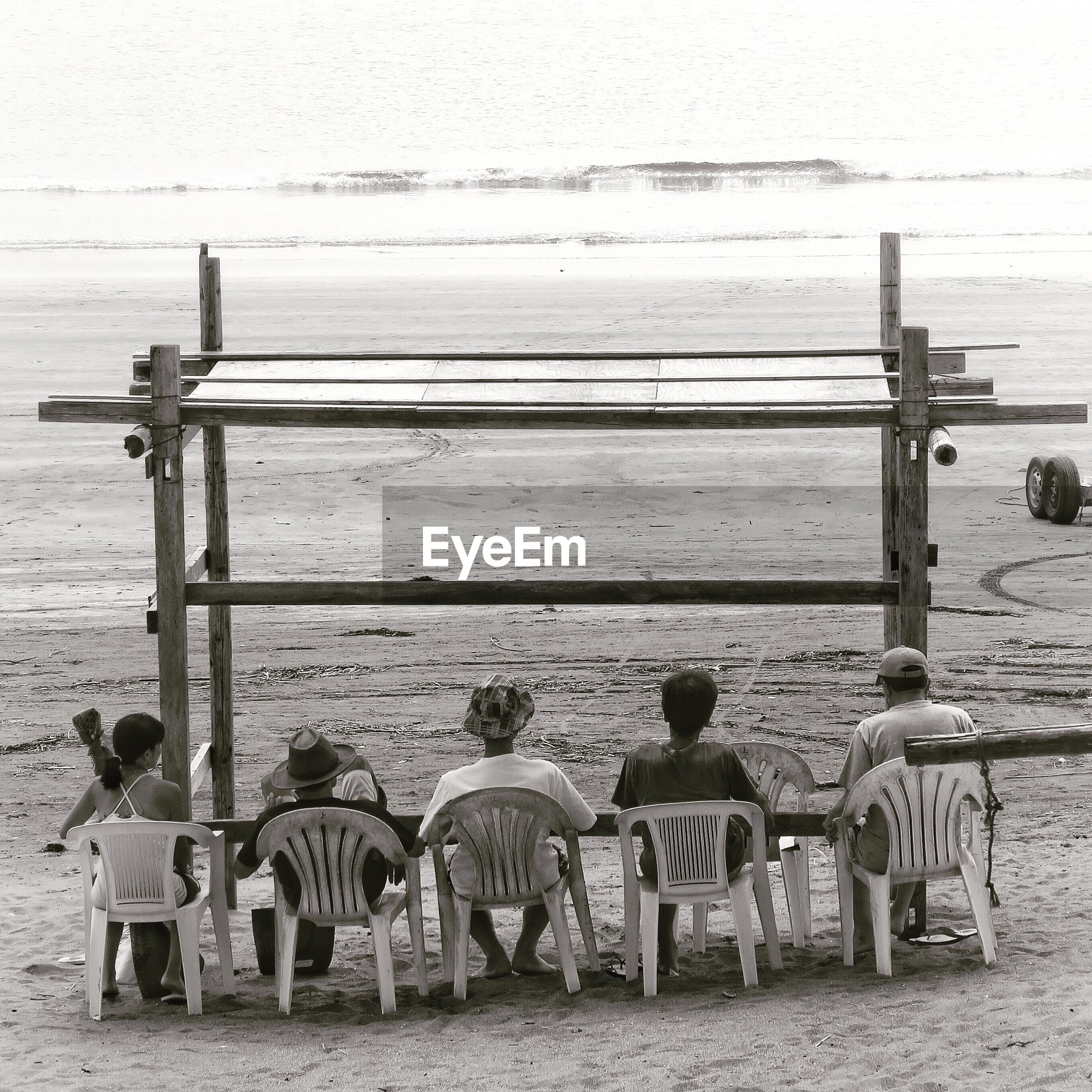 Rear view of people sitting under shed at beach