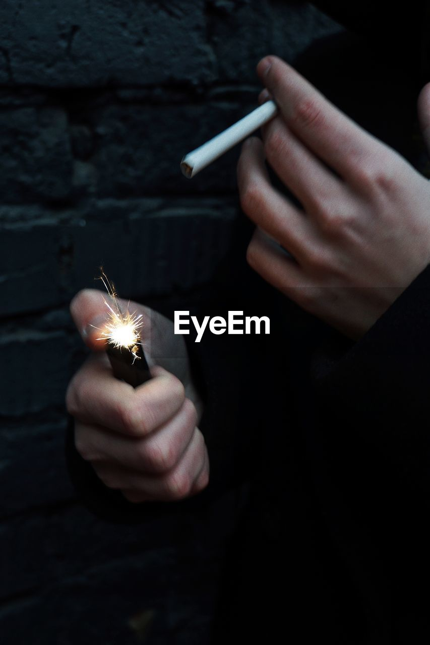 Close-up of person igniting cigarette with lighter