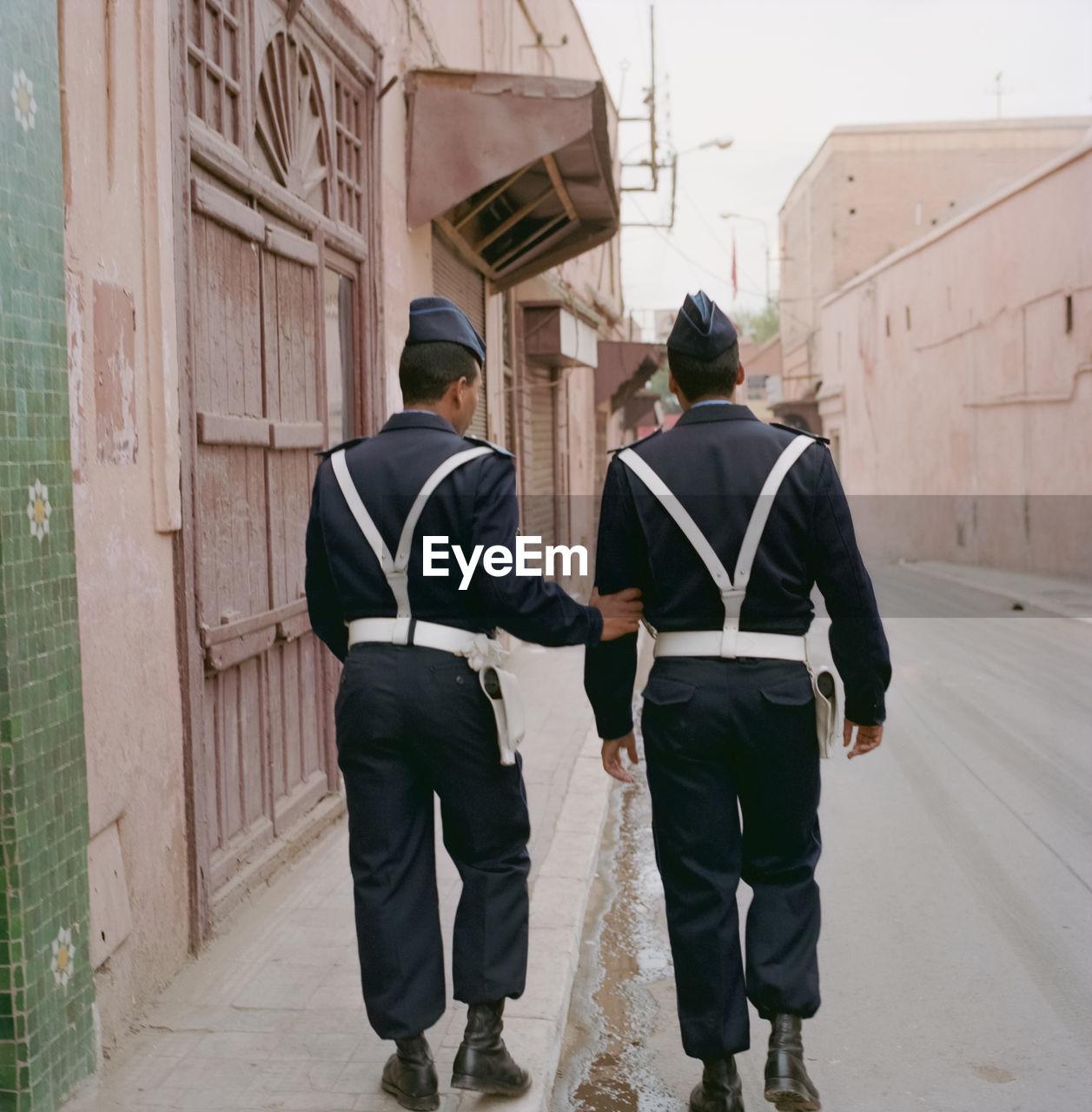 REAR VIEW OF MEN WALKING ON COBBLESTONE STREET