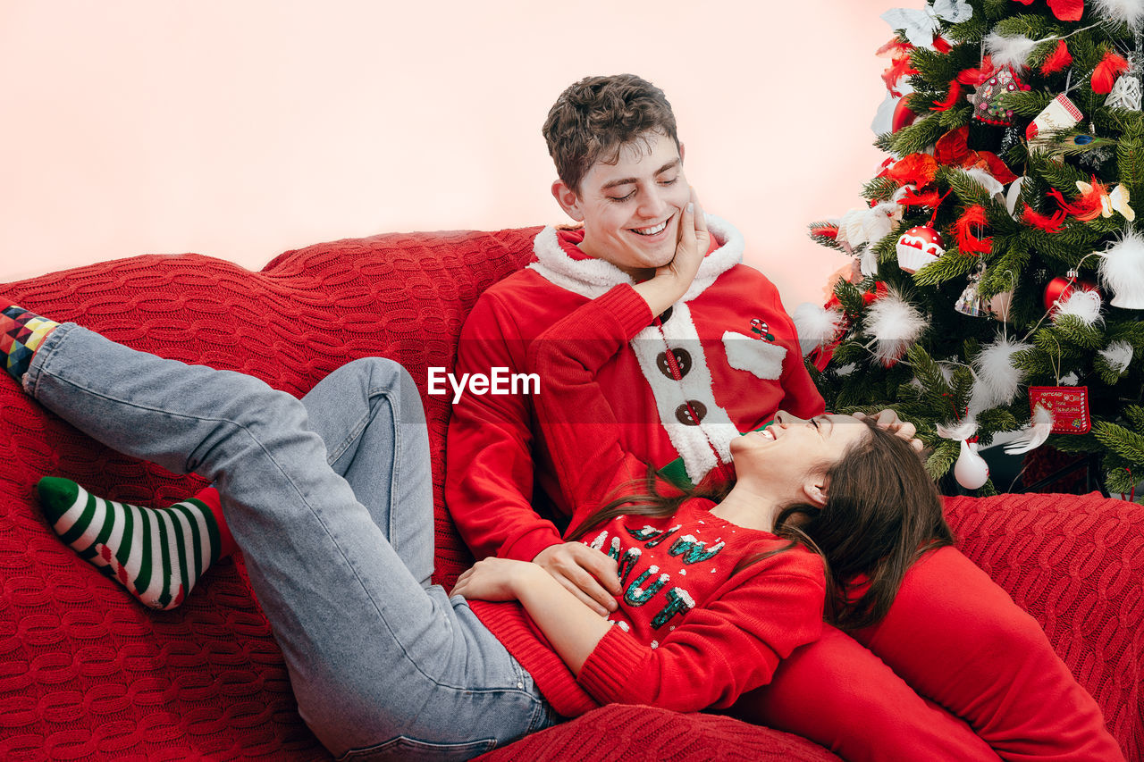 Happy Couple On Sofa At Home During Christmas