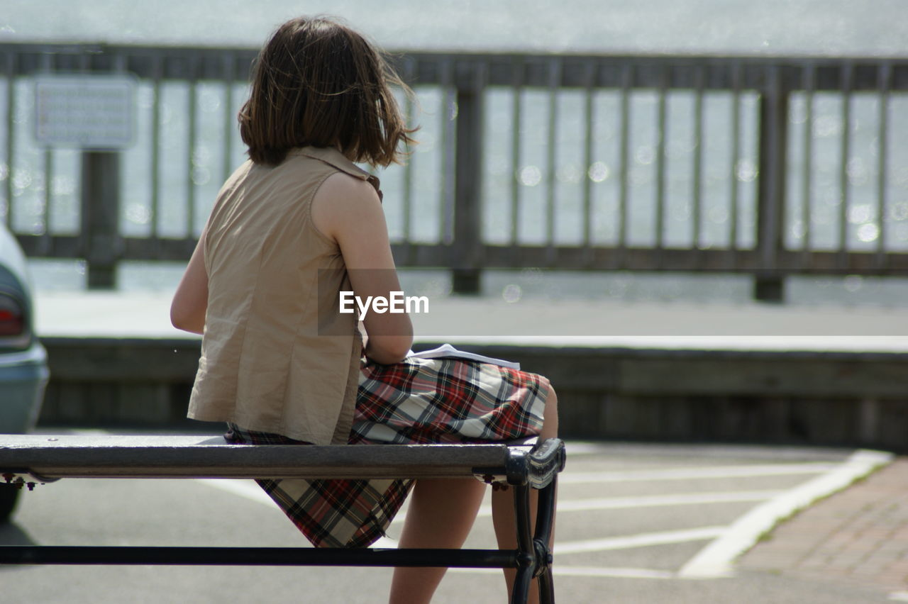 Rear View Of Woman Sitting On Bench On Pier