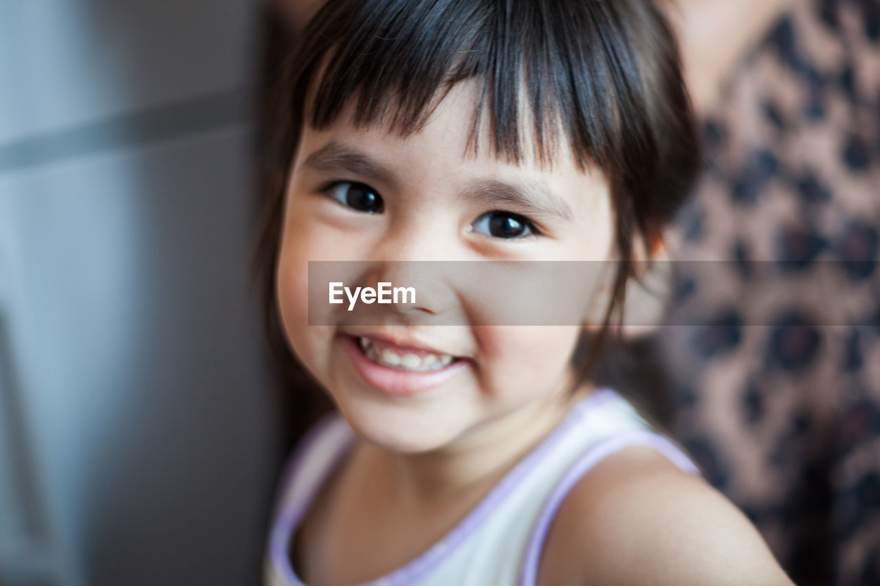 Close-up portrait of smiling girl at home